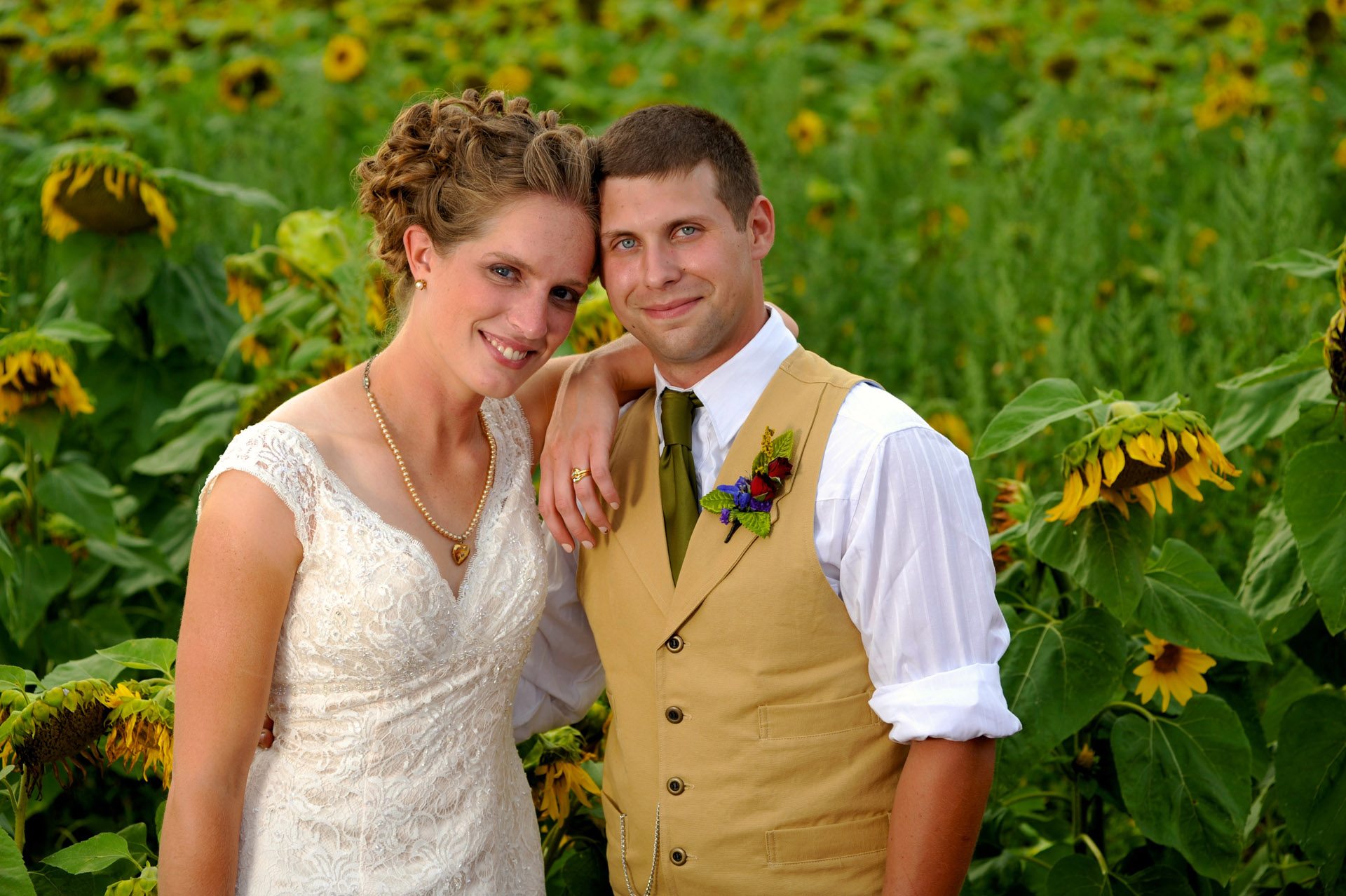 Michigan country wedding wedding photographer pose in amongst sunflowers at his family's farm at this Michigan country wedding.