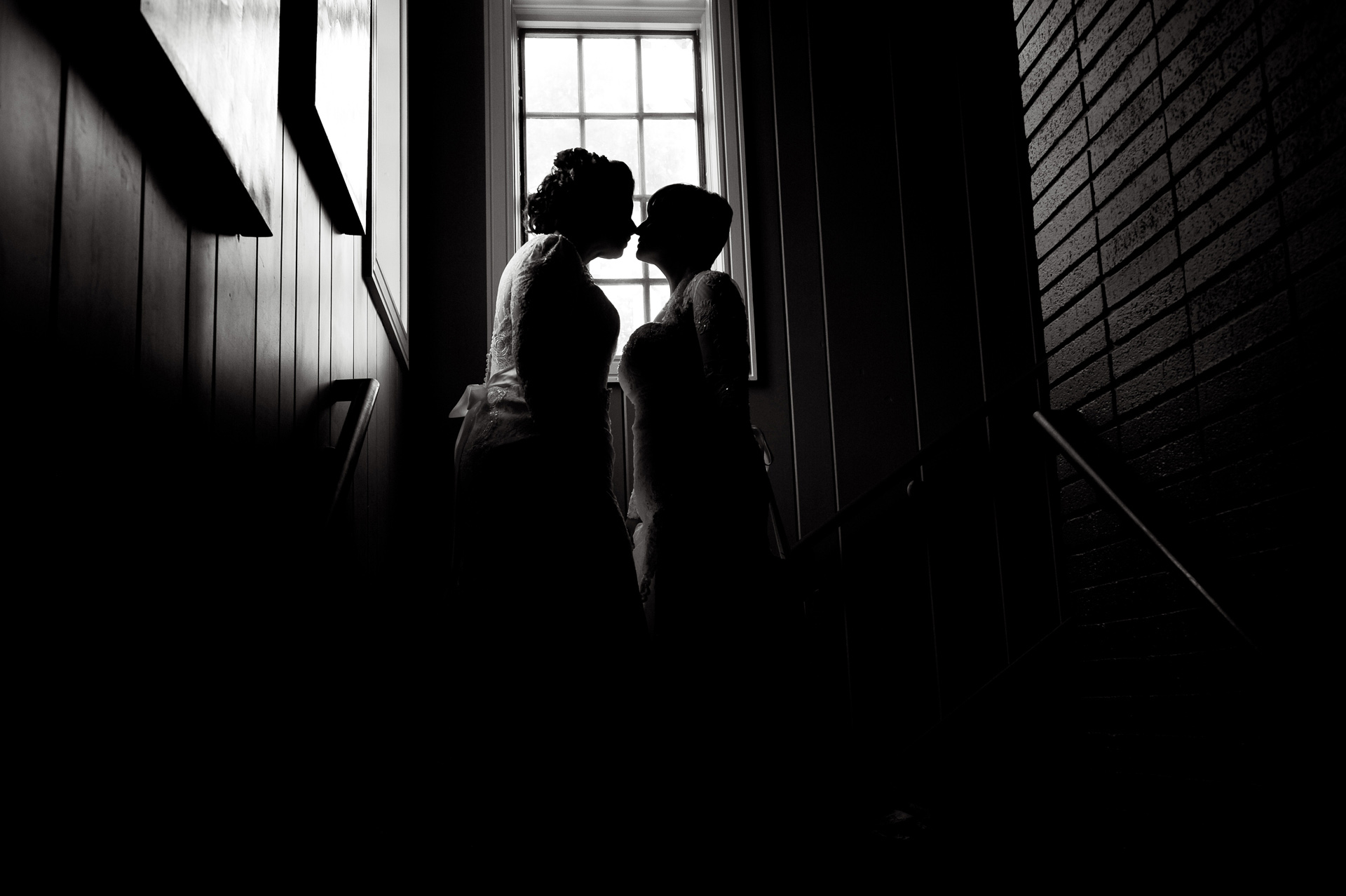 Michigan same sex wedding wedding photographer's photo of Jennifer and Emily kiss in silhouette at the restaurant after their Michigan same sex wedding in Livonia, Michigan.
