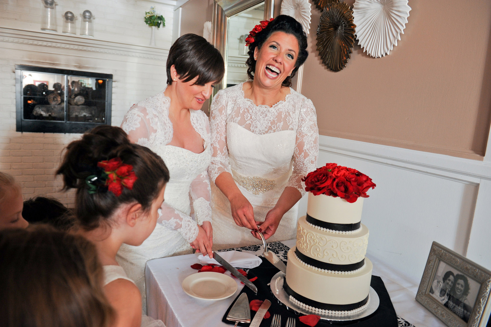 Michigan same sex wedding wedding photographer's photo of Jennifer and Emily cut the cake after their wedding ceremony at the Michigan same sex wedding in Livonia, Michigan.