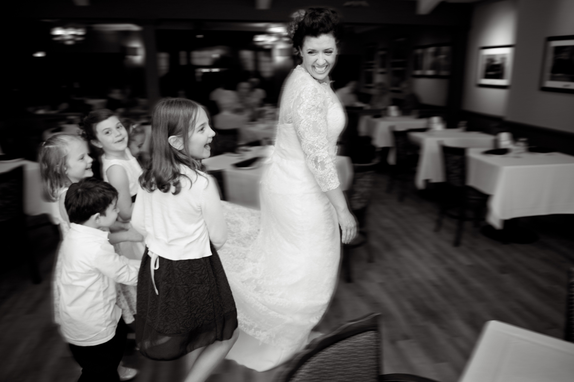 Michigan same sex wedding wedding photographer's photo of Emily and her entourage of bustle wranglers pass through the restaurant after her Michigan same sex wedding in Livonia, Michigan.
