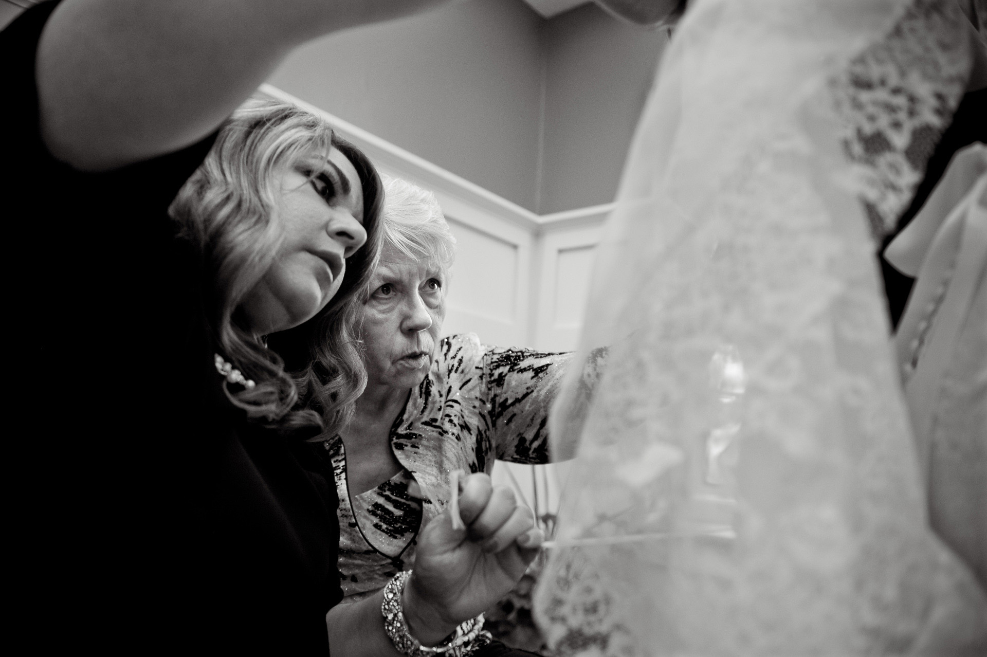 Michigan same sex wedding wedding photographer's photo of the mother of the bride and a friend trying to figure out a bustle after a Michigan same sex wedding in Livonia, Michigan.