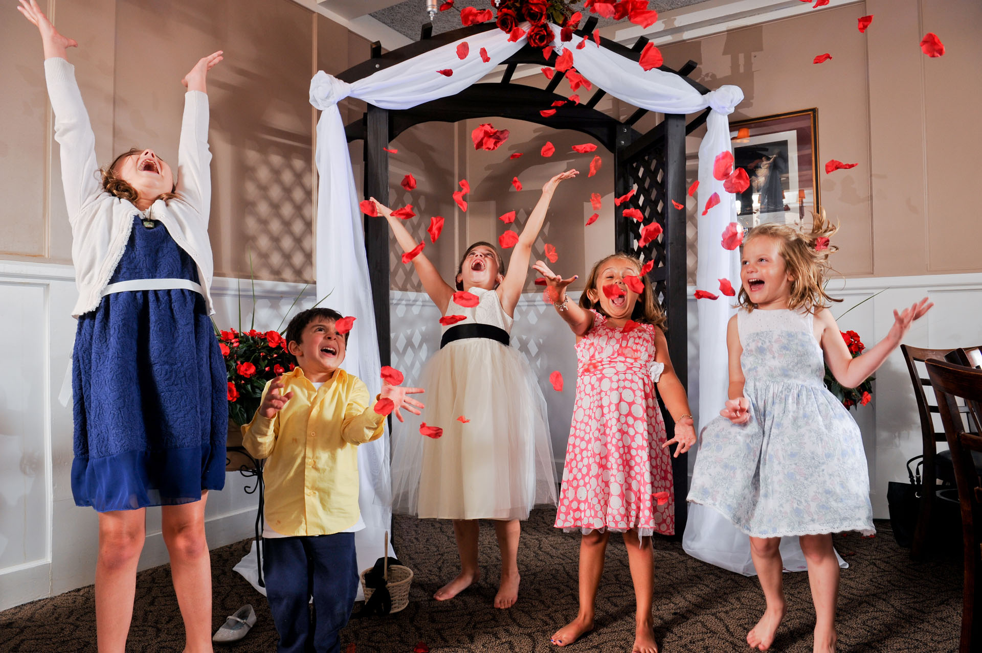 Michigan same sex wedding wedding photographer's photo of kids happily flinging rose petals in the air after a wedding ceremony at the Michigan same sex wedding in Livonia, Michigan.
