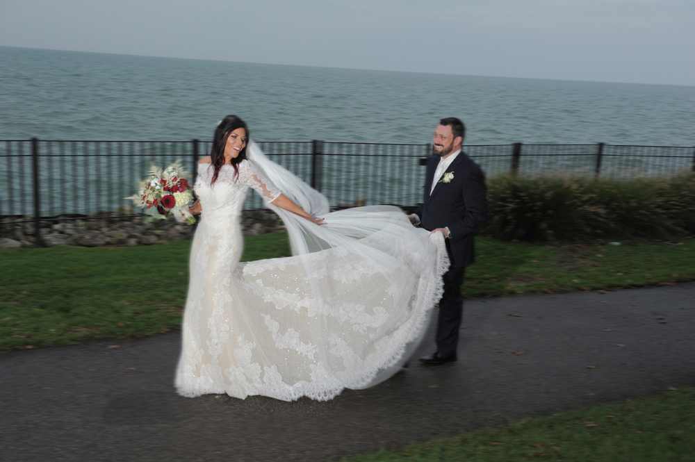 A Grosse Pointe, Michigan groom holds his bride's wedding dress train during their wedding at Pier Park in Grosse Pointe Michigan.