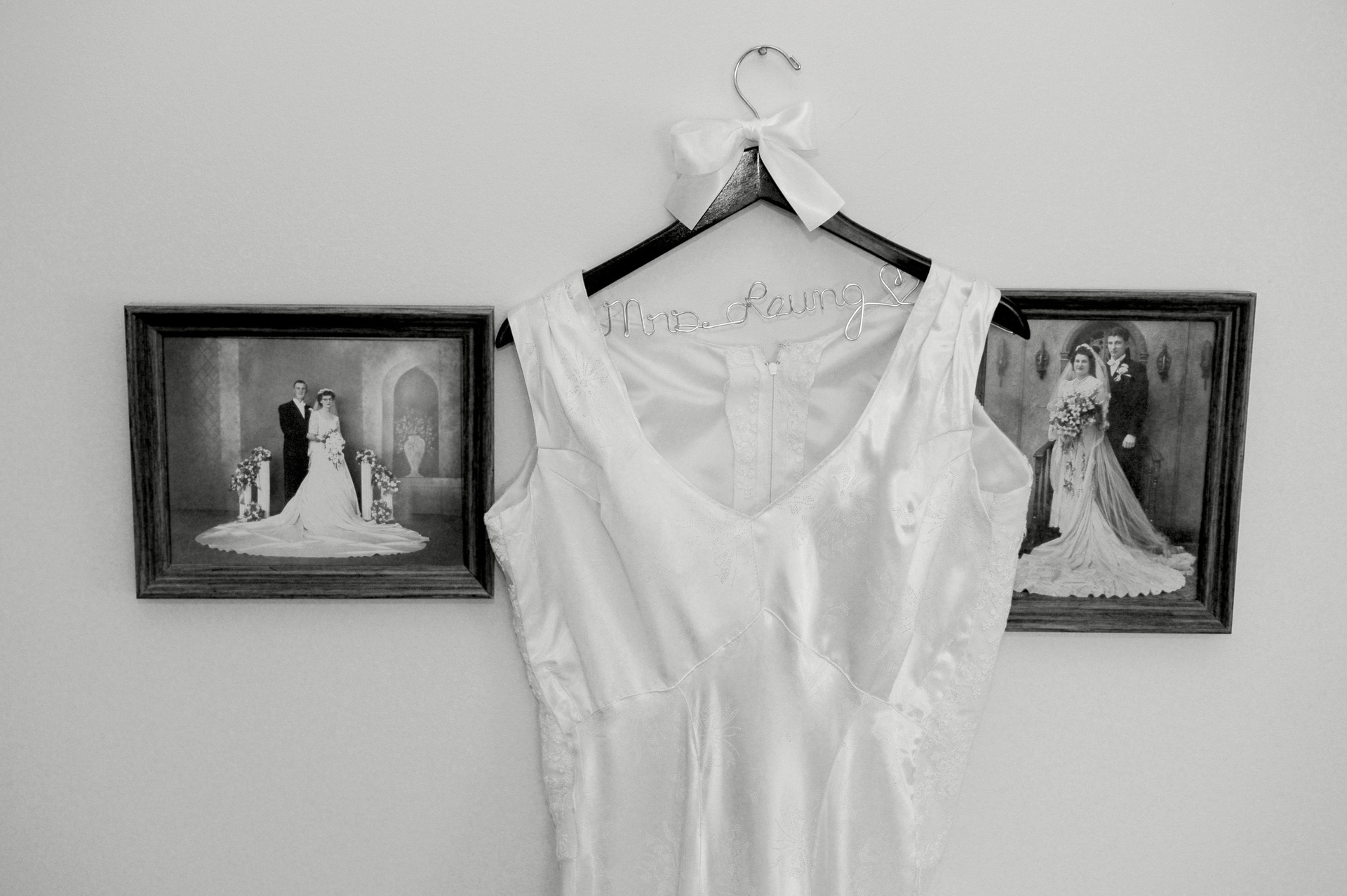 Troy and Rochester, Michigan wedding photographer's photo of the bride's wedding dress hanging in between photos of wedding photos of her mom and grandmother wearing the same dress in Troy, Michigan.