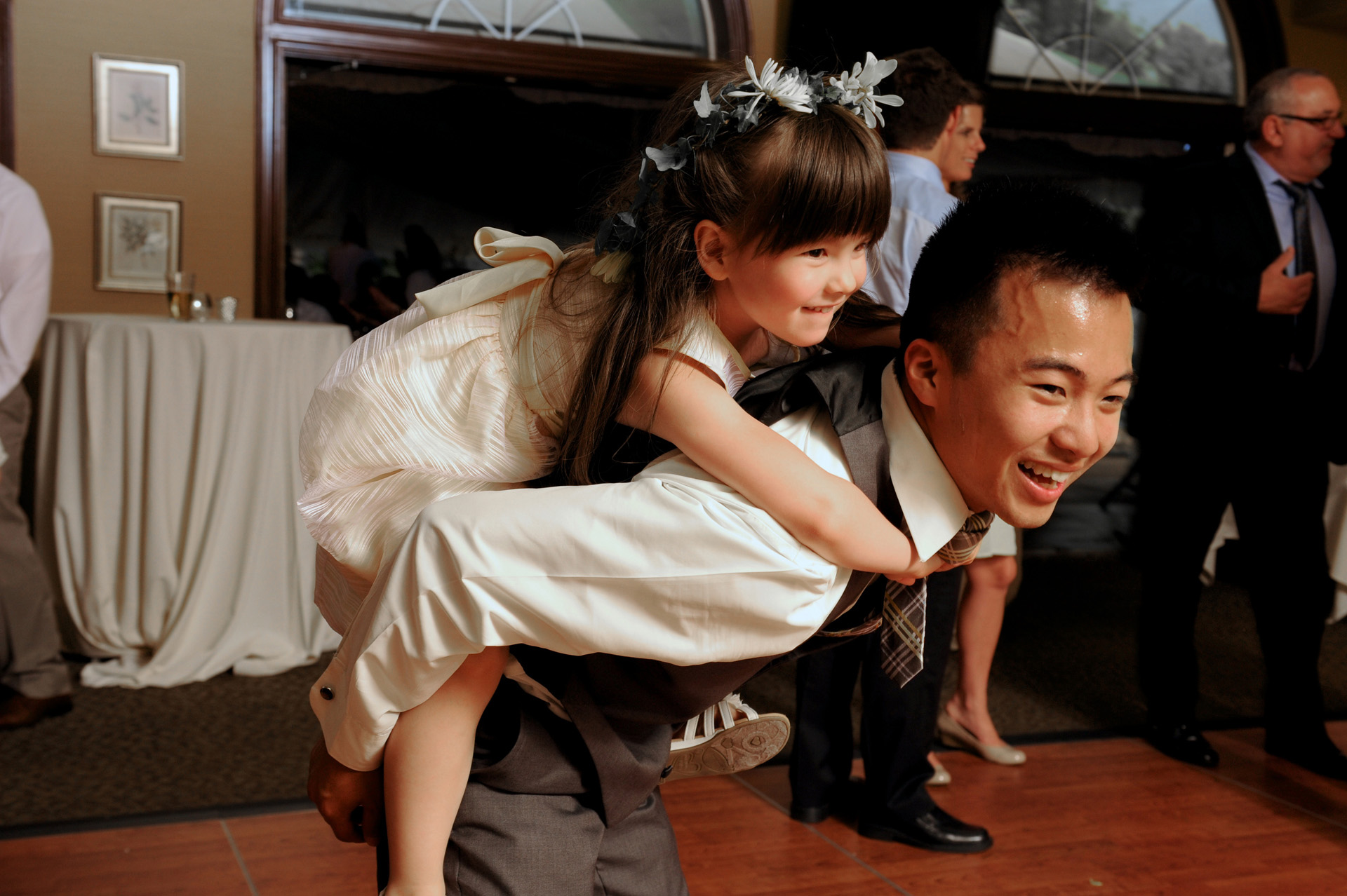 Pine Trace Golf Club wedding photographer's photo of a groomsman giving the flower girl a piggy back ride during the cocktail hour at the Pine Trace Golf Club wedding in Troy and Rochester, Michigan.