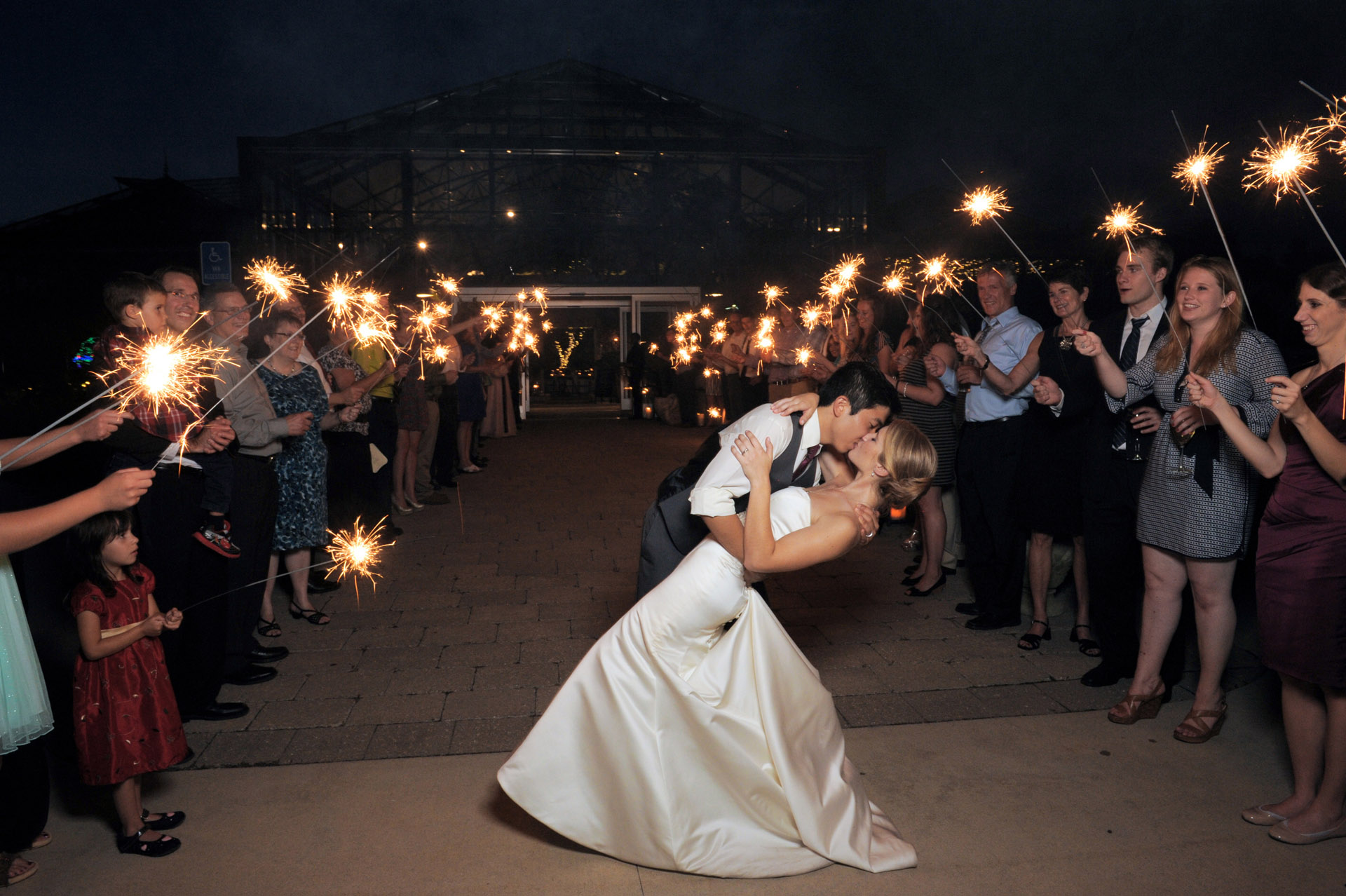 Planterra Conservatory wedding photographer's photo of the bride and groom dipping outside during a sparkler exit at the Planterra Conservatory in West Bloomfield, Michigan.