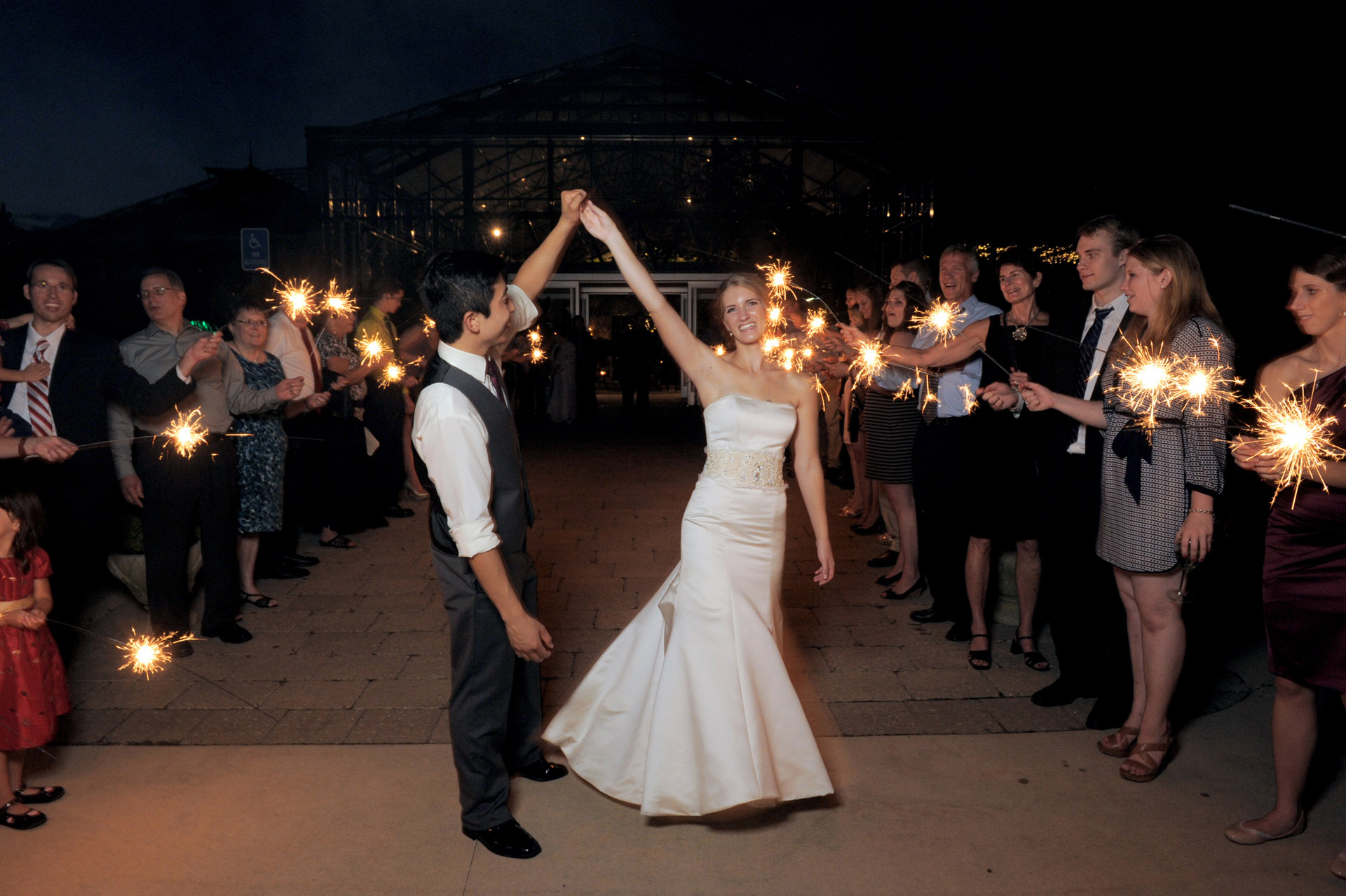 Planterra Conservatory wedding photographer's photo of bride and groom dancing outside during a sparkler exit at the Planterra Conservatory in West Bloomfield, Michigan.