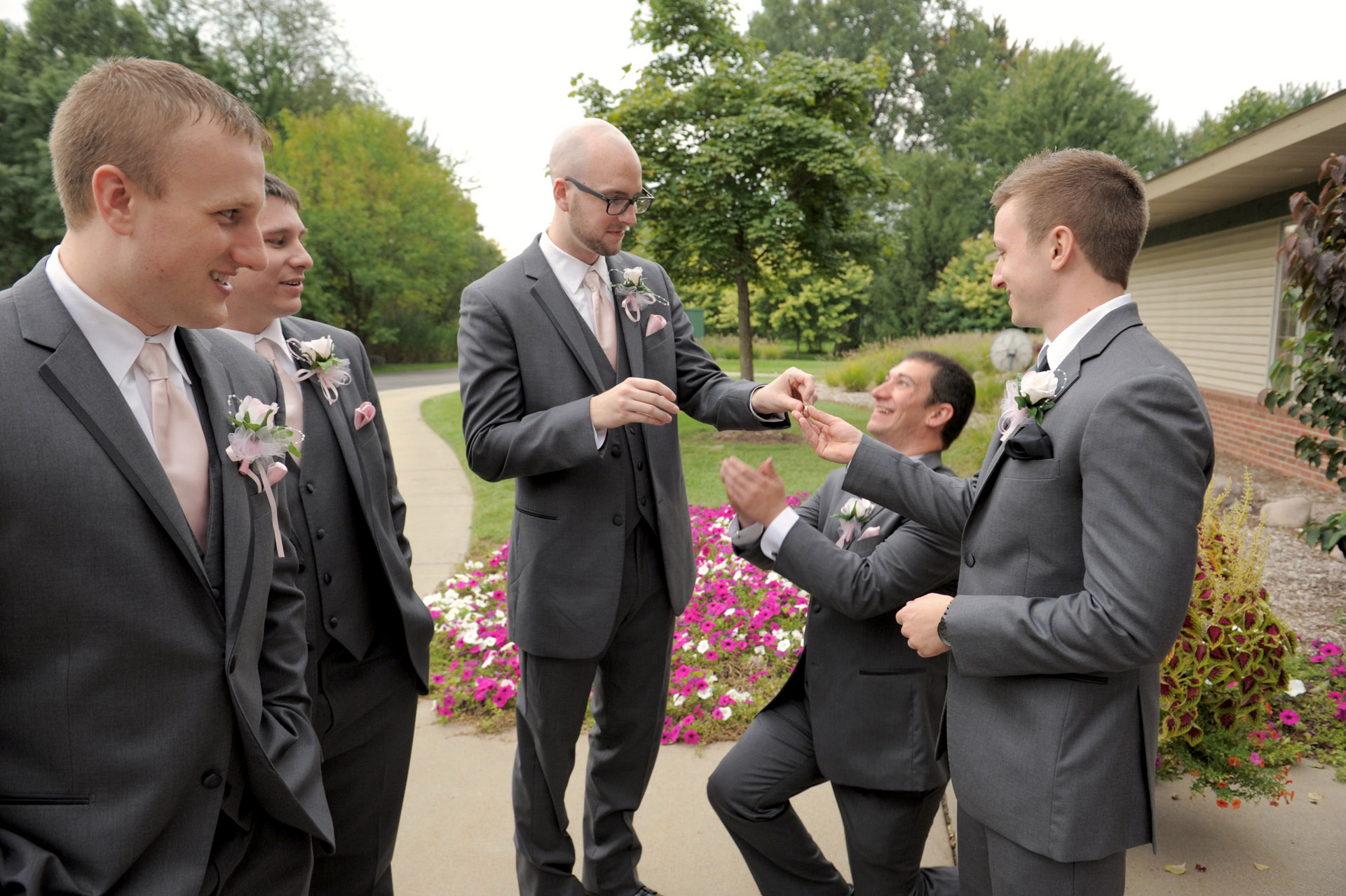 Woodlands of Van Buren in Wayne, Michigan wedding photographer's photo of the groomsmen goofing around pretending to propose the each other after a wedding at the The Woodlands of Van Buren in Wayne, Michigan.