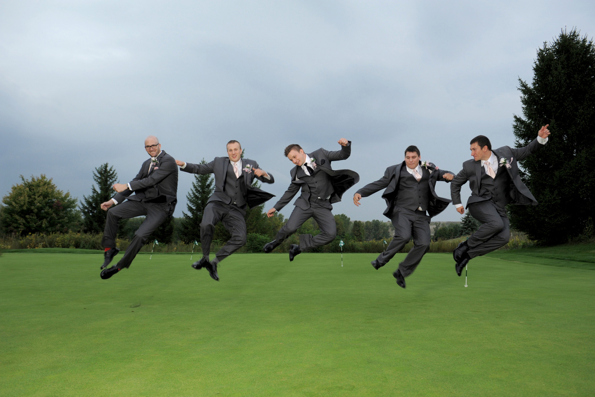 The Woodlands of Van Buren in Wayne, Michigan wedding photographer's photo of  the groomsmen clicking their heels which was their idea of something they like to do after the wedding at the The Woodlands of Van Buren in Wayne, Michigan.