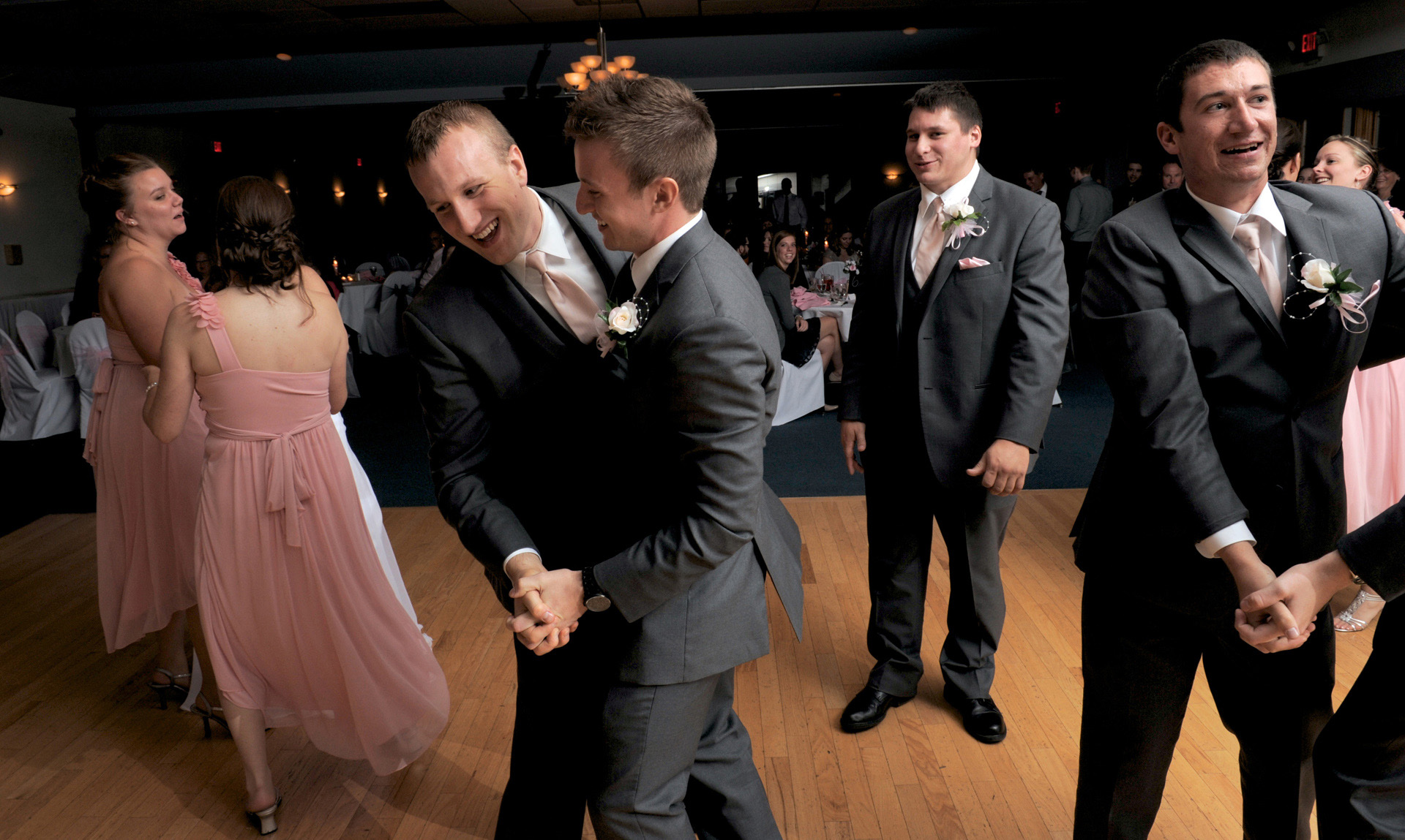 The Woodlands of Van Buren in Wayne, Michigan wedding photographer's photo of the groomsmen dance with the groom slow dance style after their wedding at the The Woodlands of Van Buren in Wayne, Michigan.