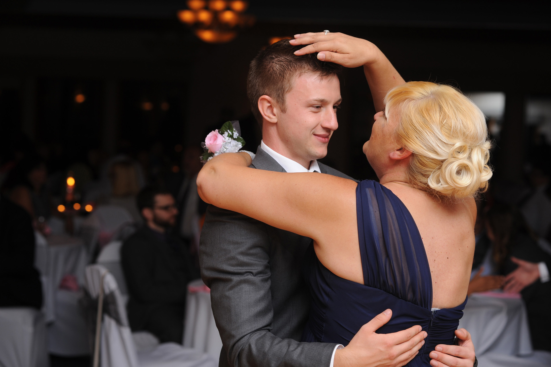 The Woodlands of Van Buren in Wayne, Michigan wedding photographer's photo of the mother of the groom pats her son's head after their mother / son dance at the wedding at the The Woodlands of Van Buren in Wayne, Michigan.