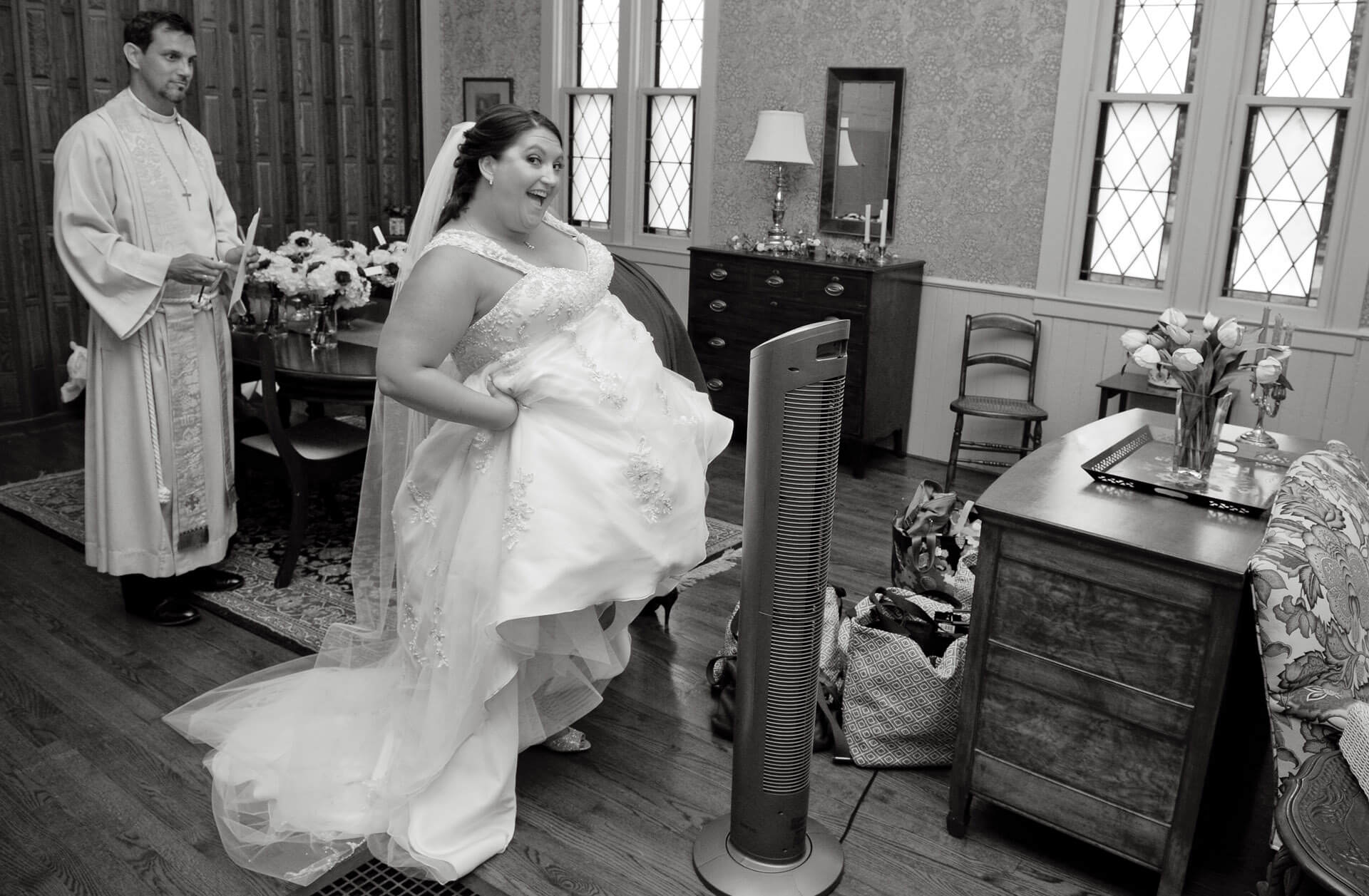 Bride hikes up her dress in Metro Detroit, Michigan to cool off just as the priest walks into the room.
