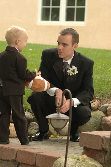 Michigan wedding photographer gets candid photos of the groom giving a pep talk to the ring bearer shortly before the wedding ceremony at English Inn in Eaton Rapids MI