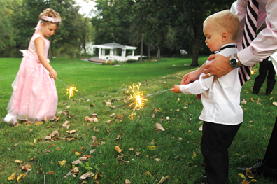 Wedding photojournalist takes lots of unposed moments of wedding guests like these where people are playing with sparklers during the wedding reception near Lansing in Michigan