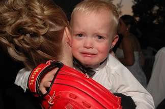 Wedding photojournalist stays through the night until things start winding down, like this ring bearer near Lansing, Michigan