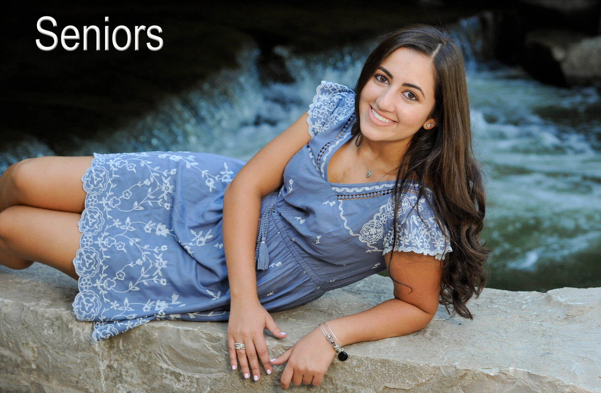 A Troy, Michigan senior poses along the bank of a river in Rochester, Michigan for her high school senior session.
