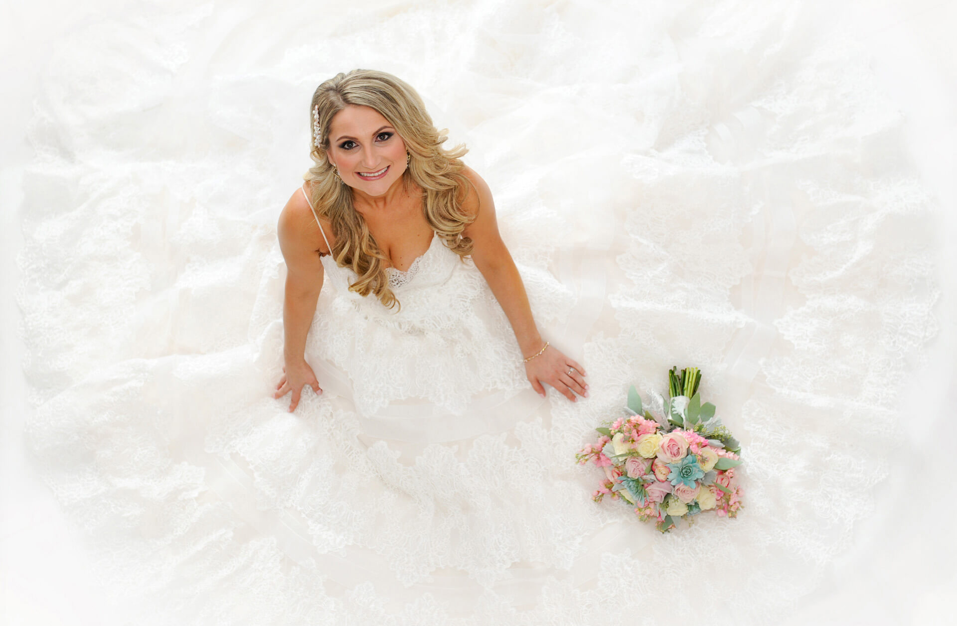 A bride sits on the floor of her home for this dramatic wedding day photo in Detroit, Michigan.