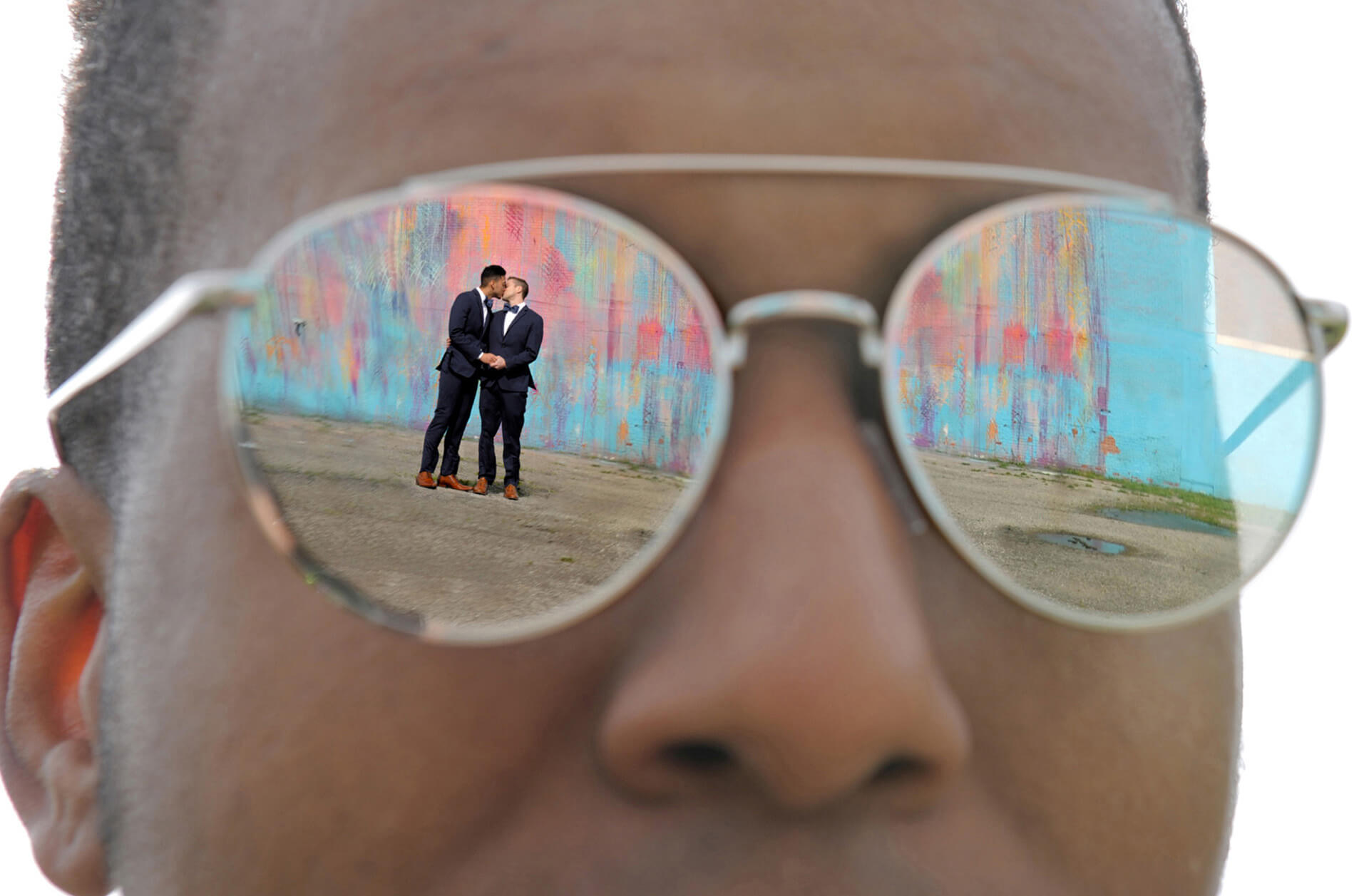 One of the groomsmen reflects two grooms in his sunglasses.