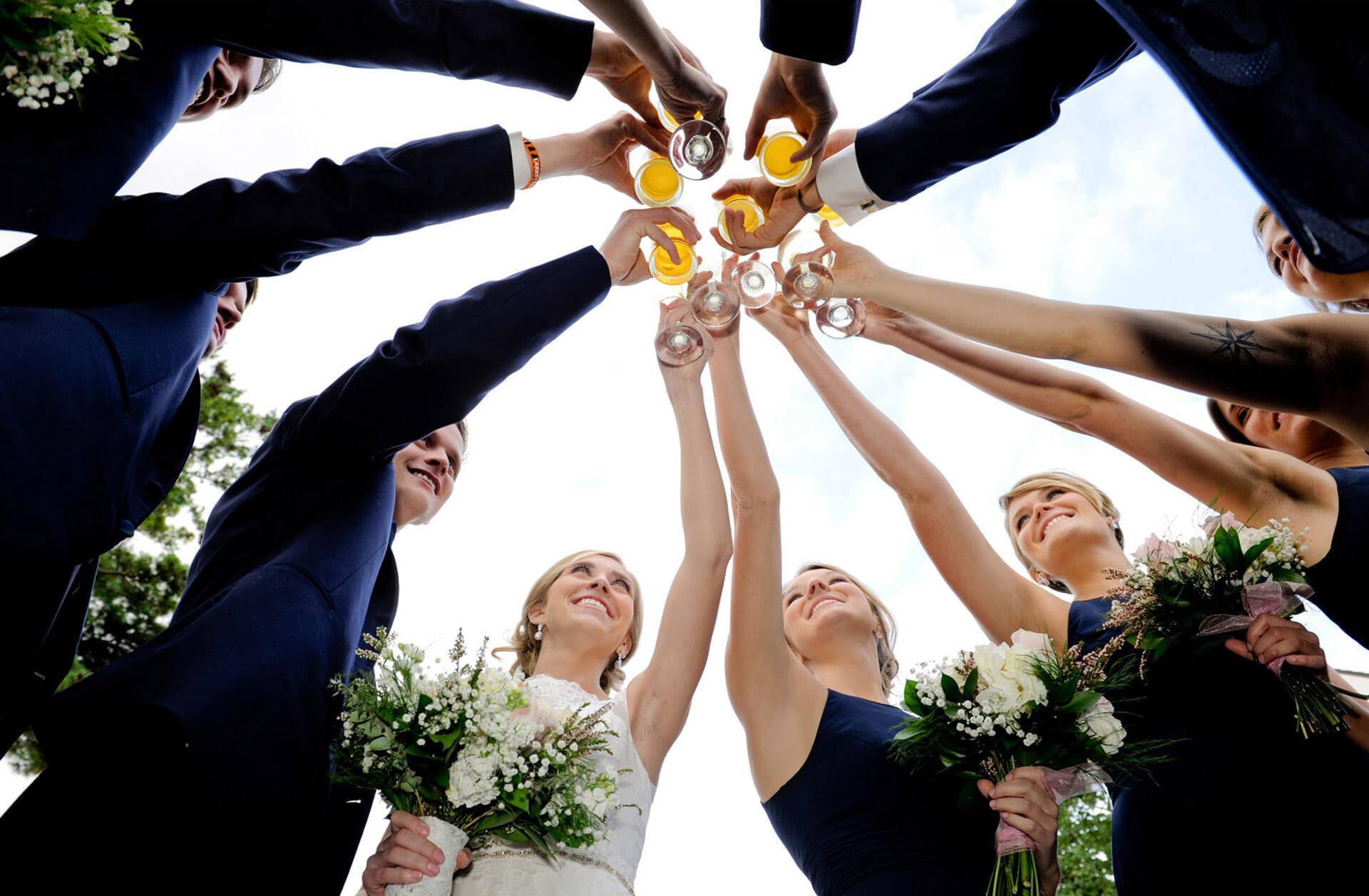 The wedding party toasts outside their Addison Oaks wedding reception in Leonard, Michigan.