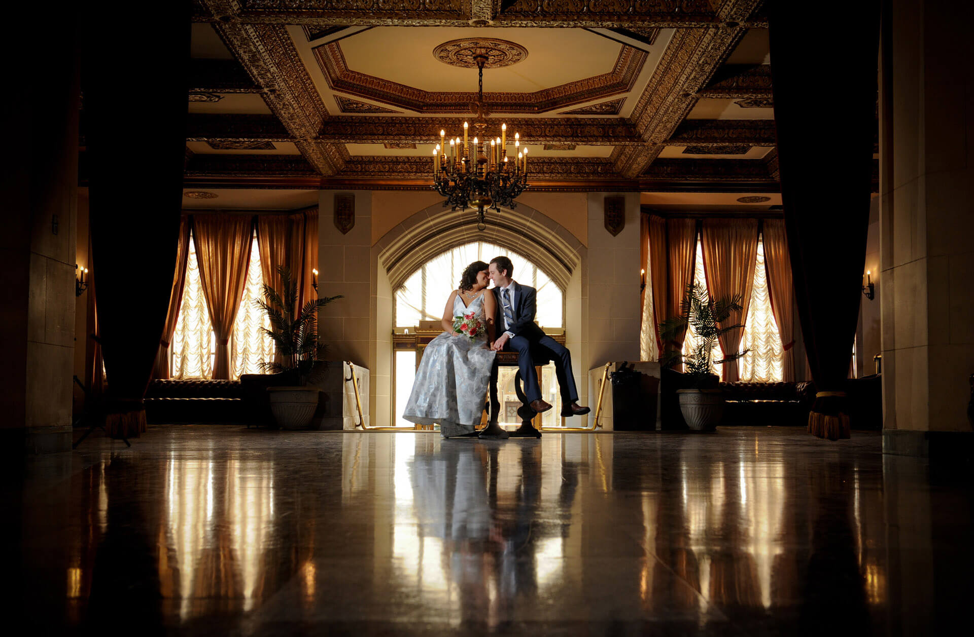 A metro Detroit, bride and groom celebrate their wedding in the lobby of the Masonic Temple downtown Detroit, Michigan.