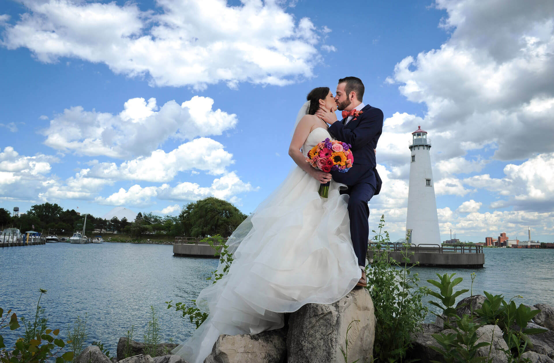 The bride and groom smooch at a lighthouse after their wedding in Detroit, Michigan.
