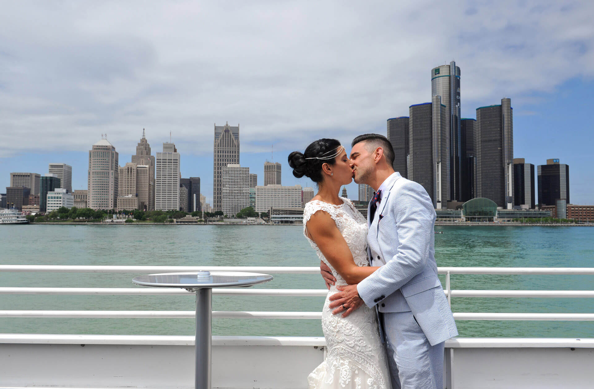 The bride and groom kiss in front of the Detroit skyline from aboard their Infinity and Ovation Yacht wedding in Michigan.