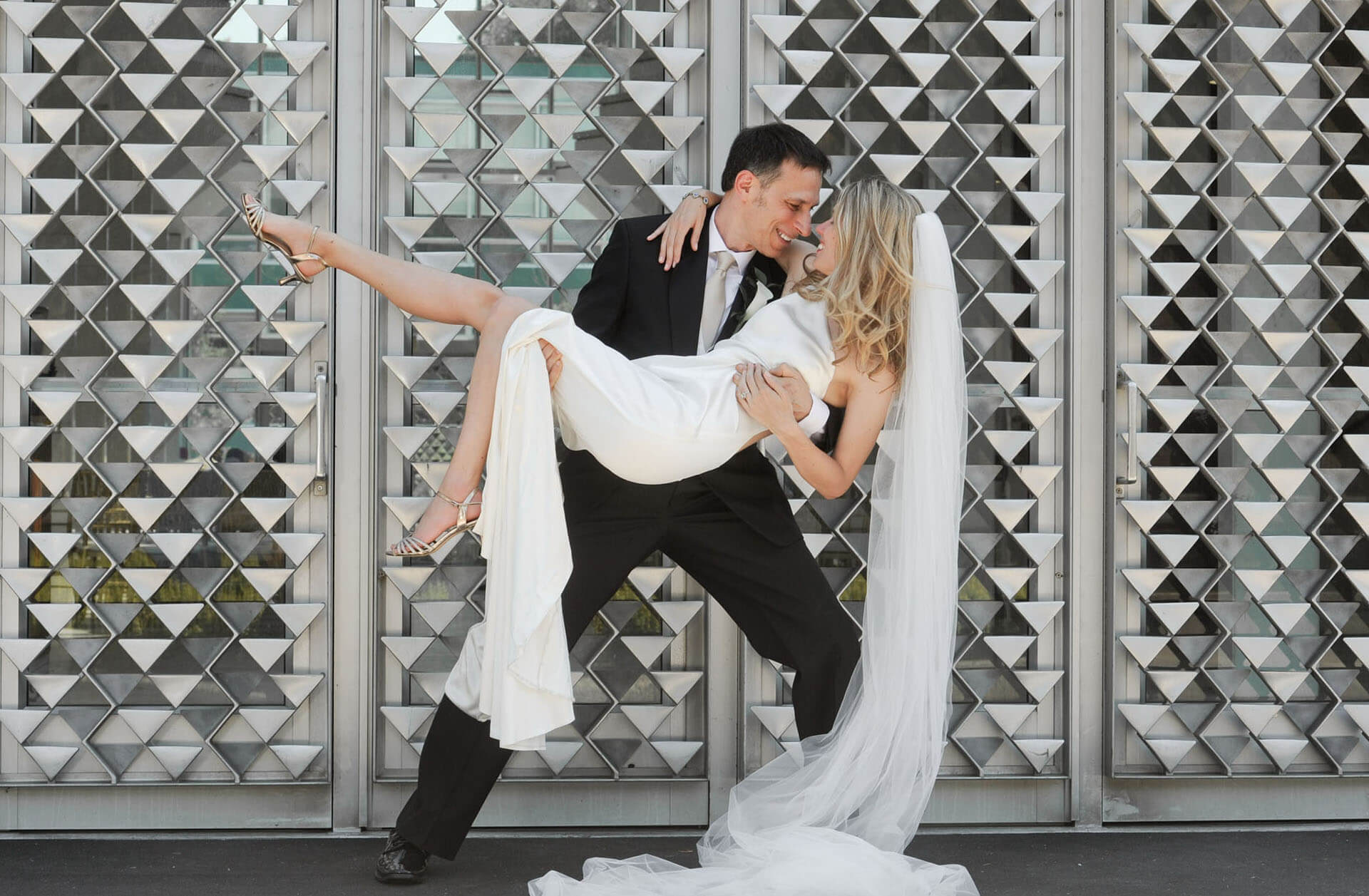 A groom picks up his bride for this fun, dramatic wedding portrait at Wayne State University in Detroit, Michigan.
