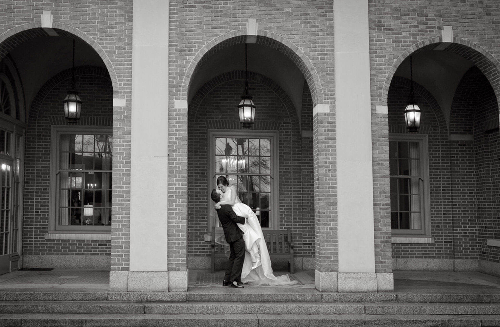 The bride and groom kiss in front of the Dearborn Inn in Detroit, Michigan.