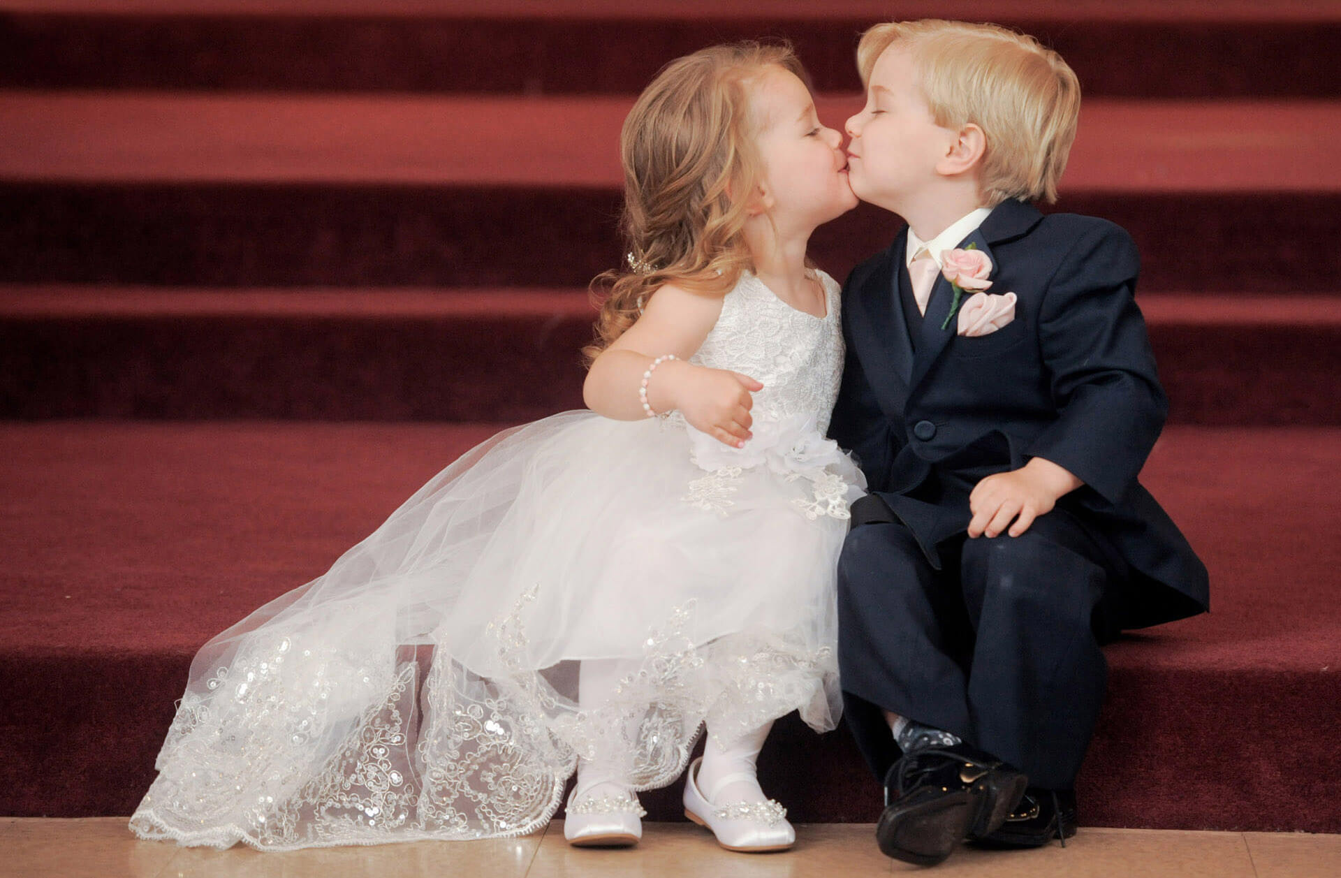 The ring bearer and flower girl share a kiss before a wedding in Metro Detroit, Michigan.