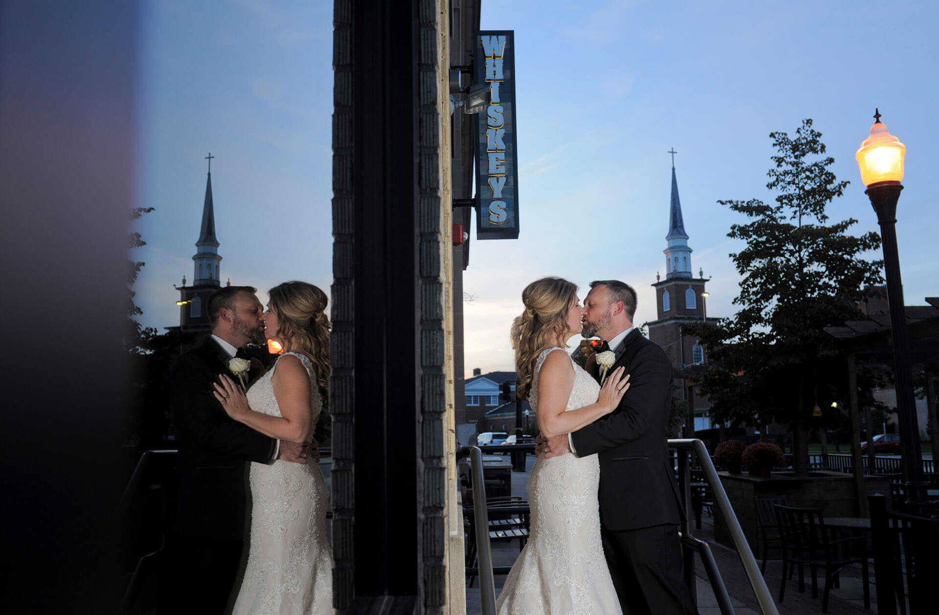 A cool sunset photo of the bride and groom reflected in the window of their reception hall Whiskeys in Wyandotte, Michigan.