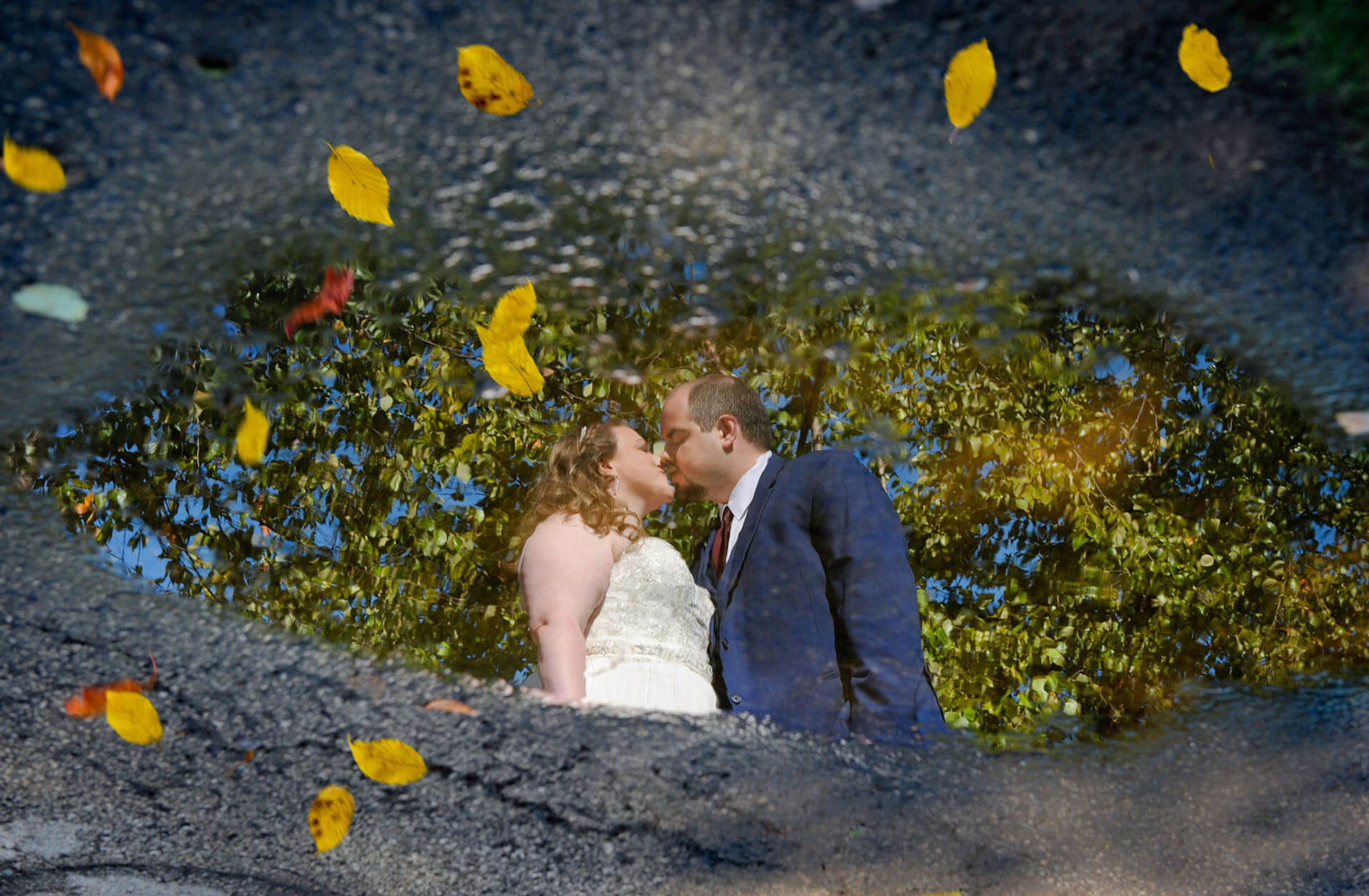 The bride and groom are reflected in a puddle with fall leaves during their wedding reception at the Freighthouse in Ypsilanti, Michigan.
