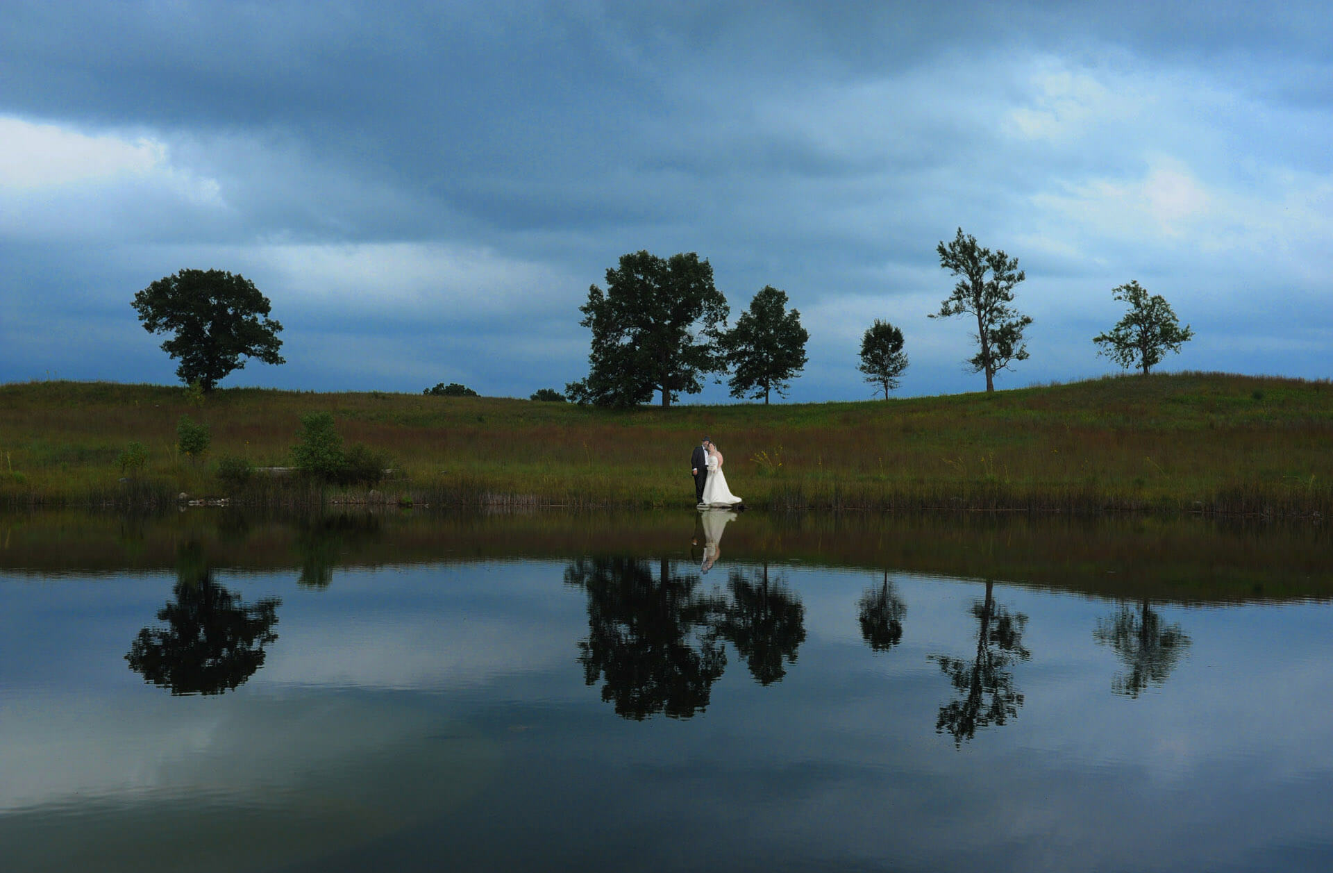 The bride and groom are reflected in the pond at Indian Springs Metropark in  Michigan.