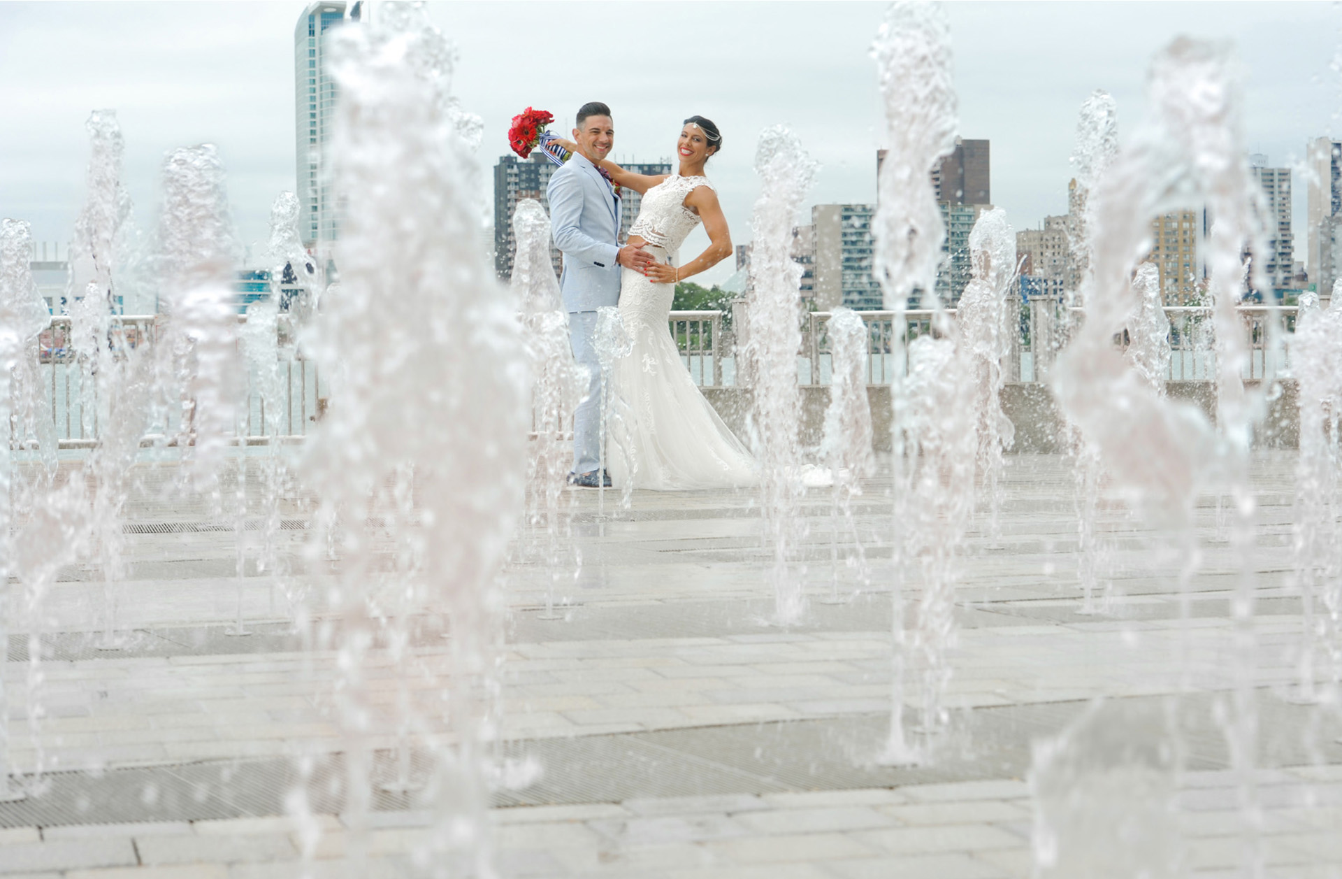 The bride and groom pose along the waterfront's spraypark before their wedding in Detroit, Michigan.