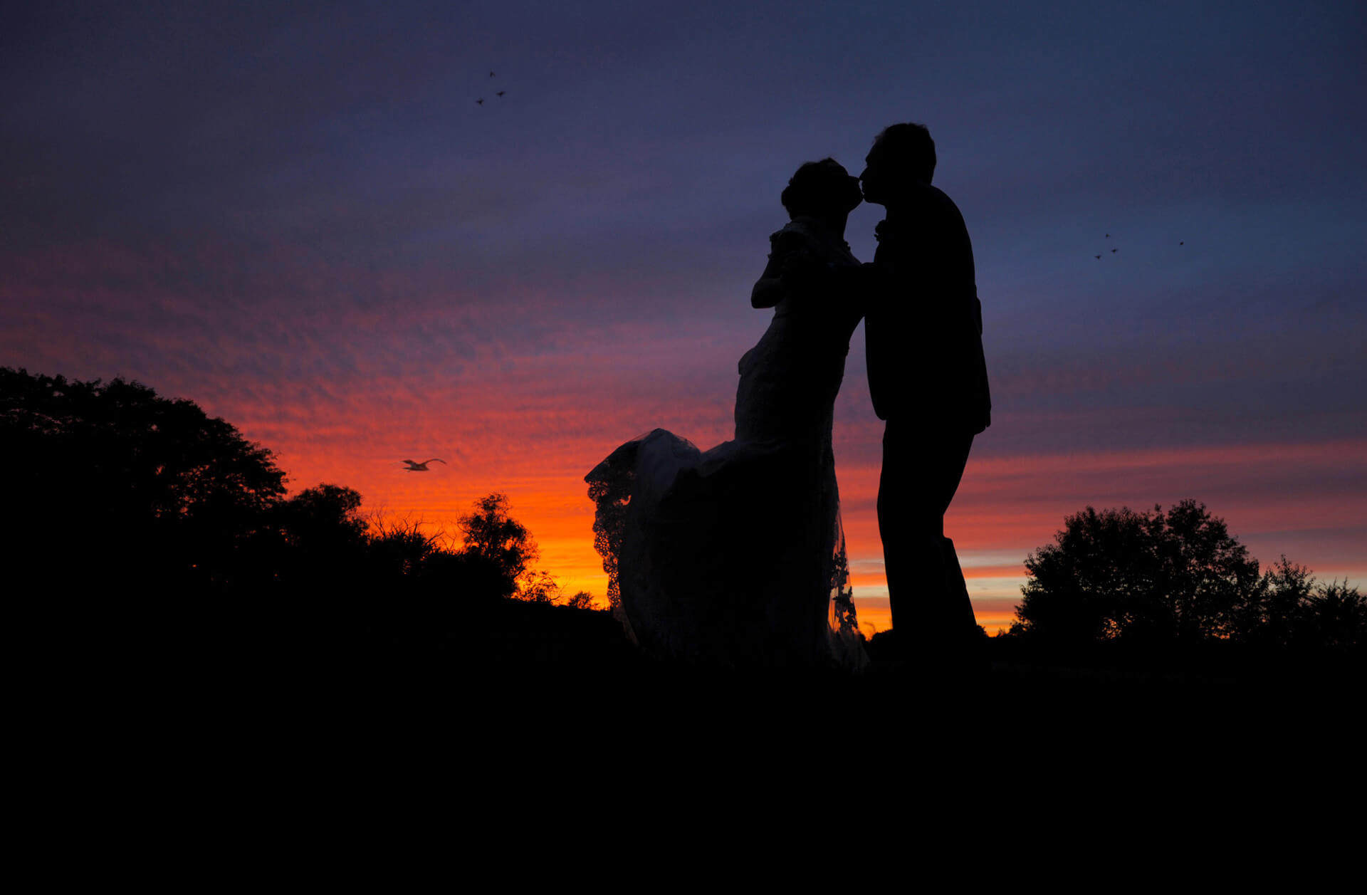 The bride and groom kiss during a gorgeous Holly, Michigan sunset during their wedding at the Holly Hotel.