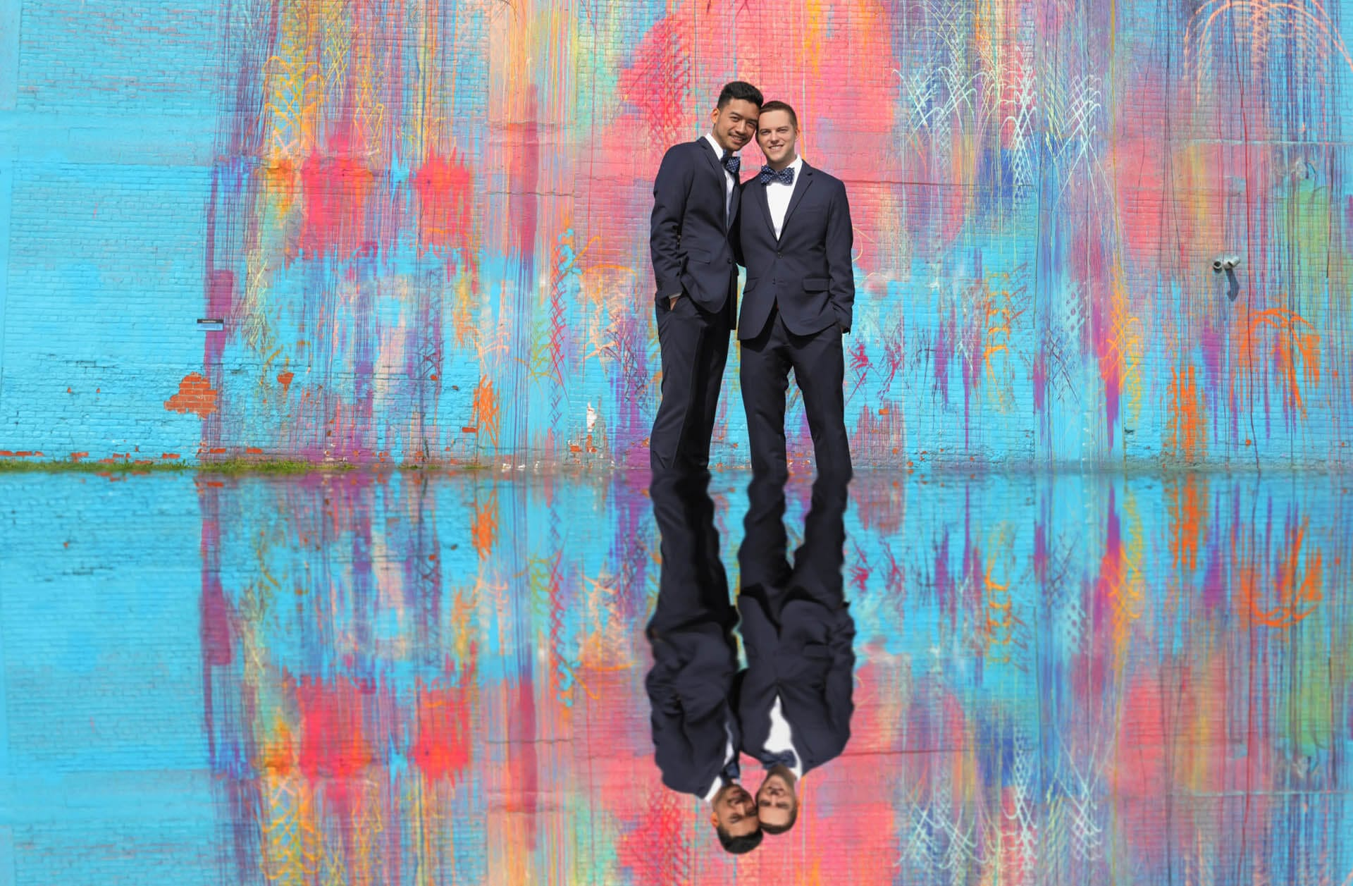 Two grooms are reflected in a puddle with the
