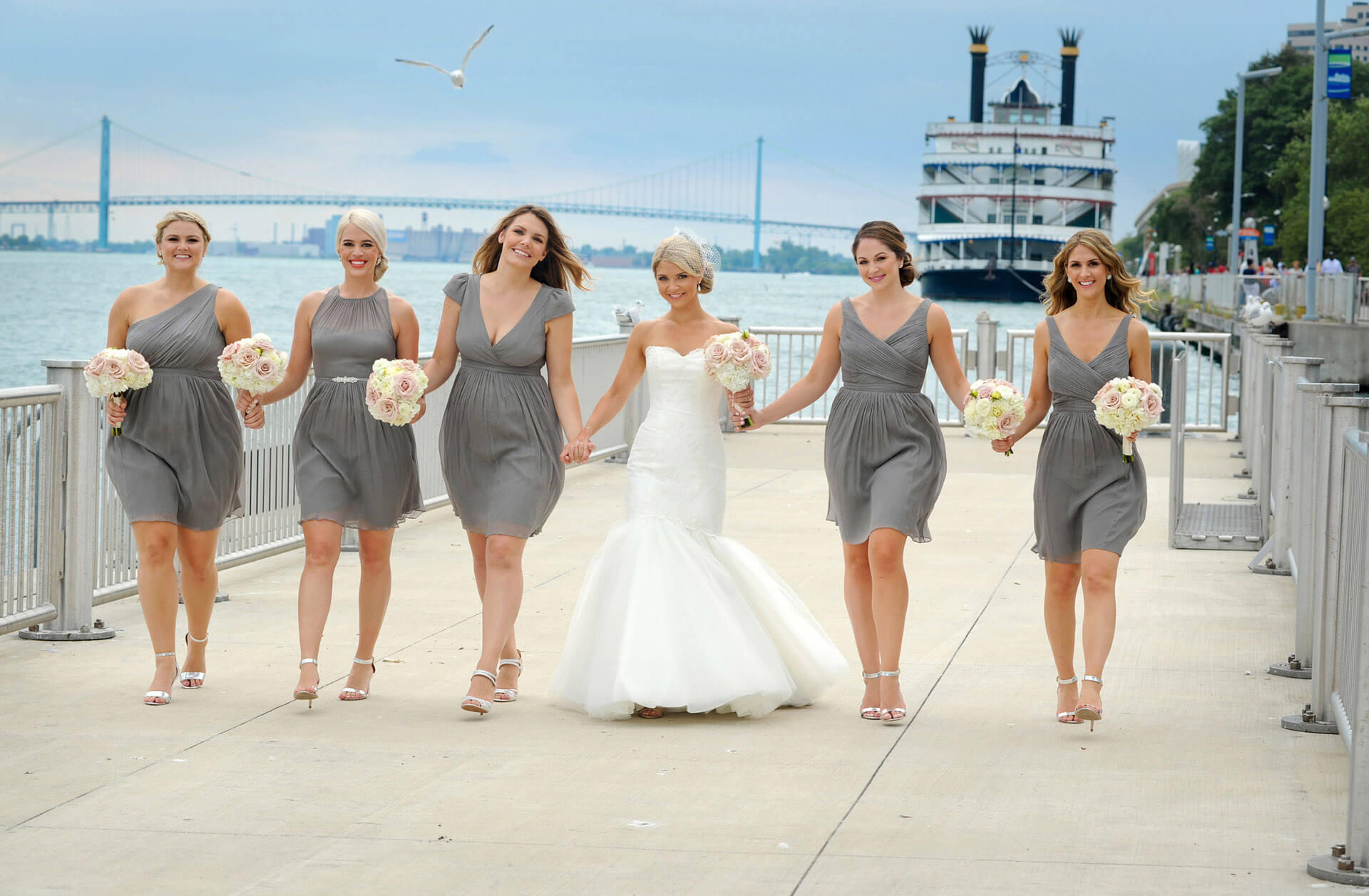 Best Michigan wedding photographer's photo of a Michigan bride and her bridesmaids walk on the boardwalk of Detroit in front of the Waterview Loft.