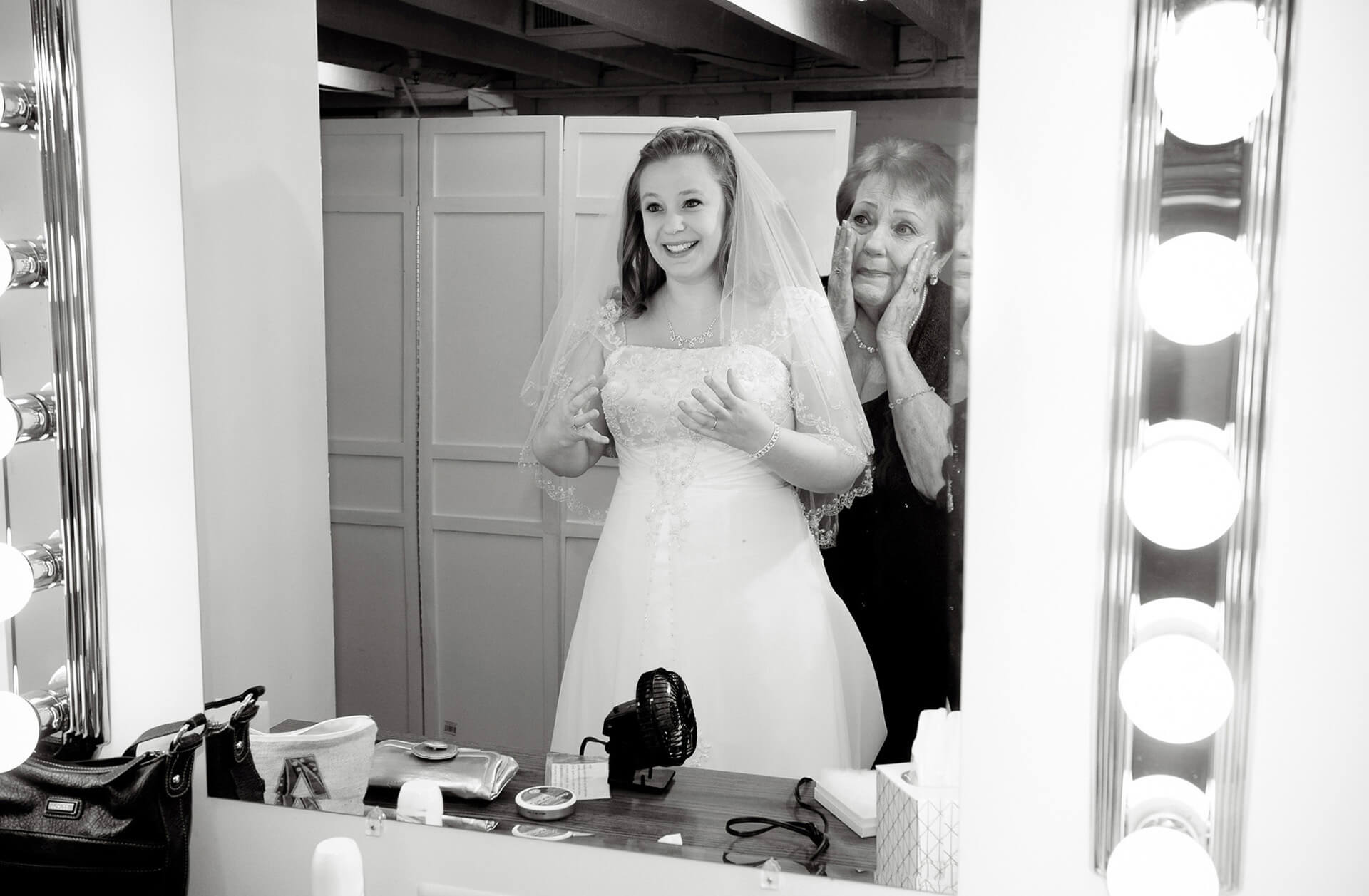A Clarkston, Michigan bride finishes her wedding preparations in a mirror as her grandmother sees her for the first time from one of Michigan's most affordable Michigan wedding photojournalists.