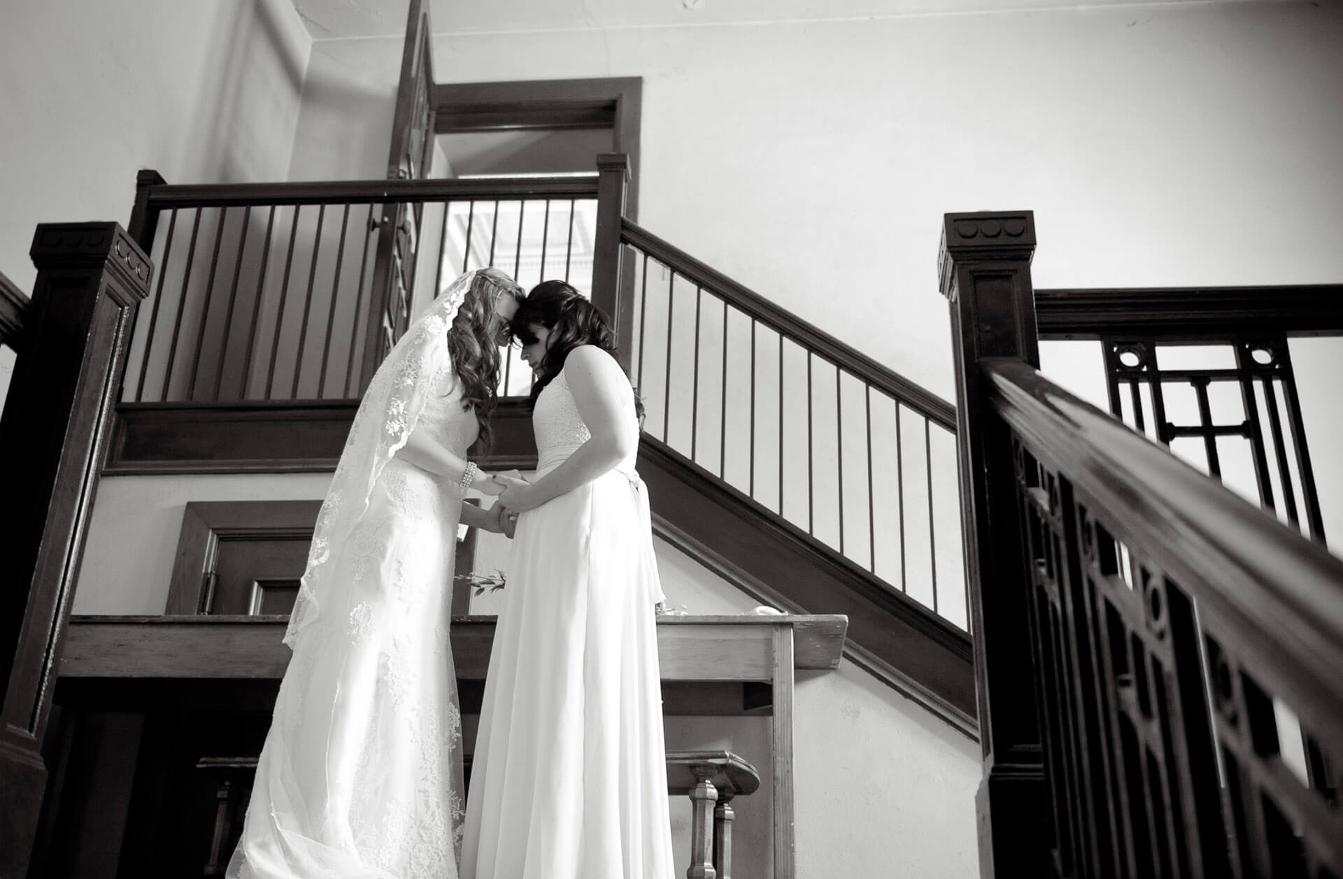 The maid of honor bows her head along with the bride in prayer just before she heads down the aisle in the photojournalist style of wedding photography taken by best, most affordable Michigan wedding photographer, Marci Curtis.