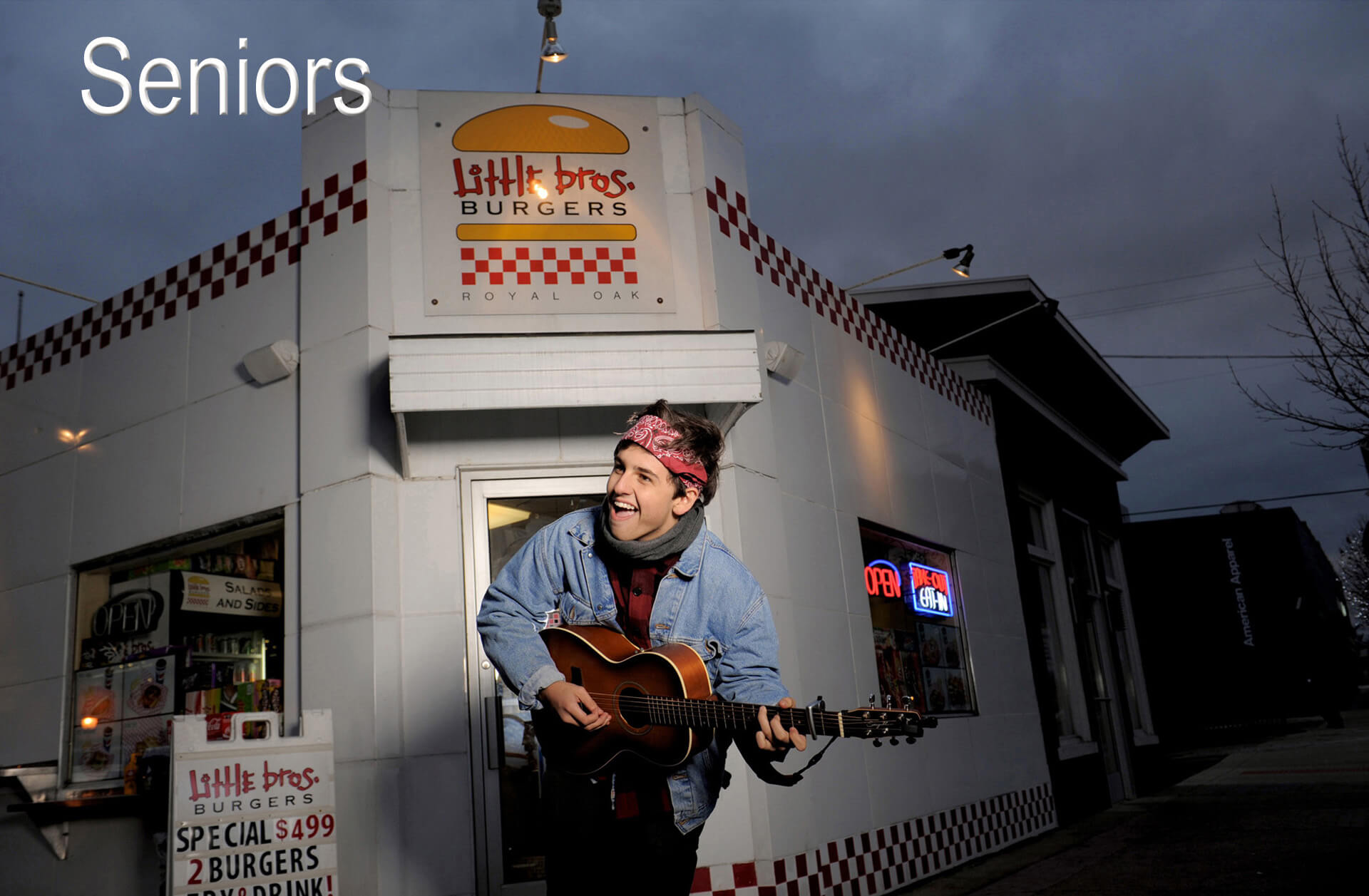 A Royal Oak, Michigan senior jams on his guitar in front of his favorite hamburger joint during his senior photo shoot featuring Marci Curtis's best Metro Detroit senior photos.