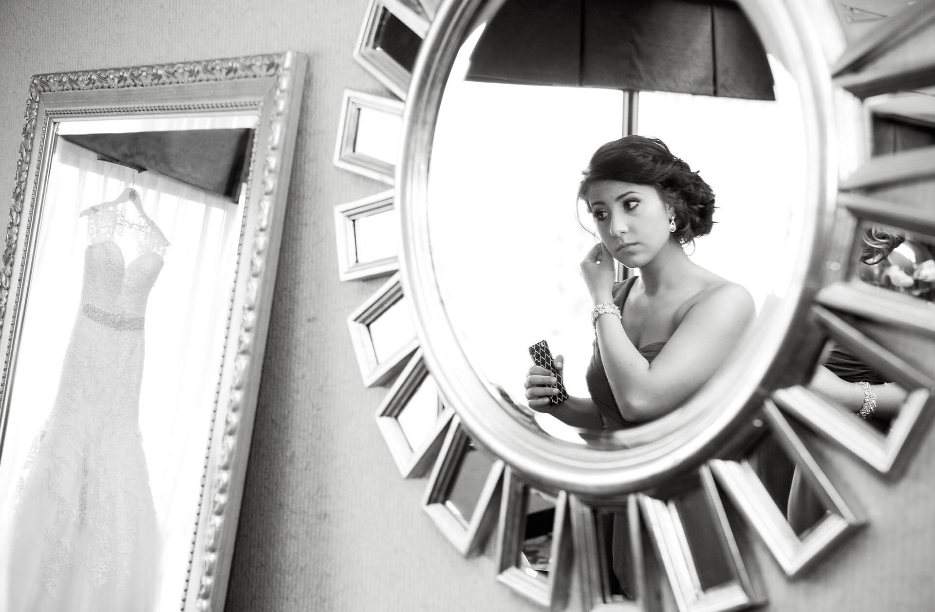 A bridesmaid gets ready in Rochester, Michigan at the hotel while the bride's dress hangs in the mirror taken by bride's favorite Michigan wedding photographer.