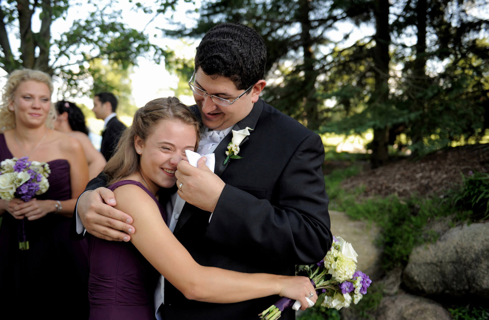 A Rochester, Michigan groom wipes away his new sister in law's tears after his wedding which capitalized on one of Michigan's best wedding photojournalists.