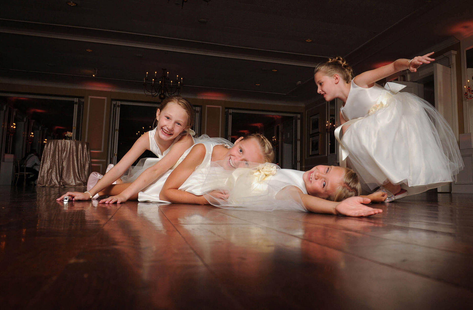 The flower girls have a spontaneous pile on in the middle of the dance floor at the Oakland Hills Country Club in Birmingham, Michigan wedding reception in this fun candid moment captured by one of the most affordable Michigan wedding photographers in Metro Detroit, Michigan.