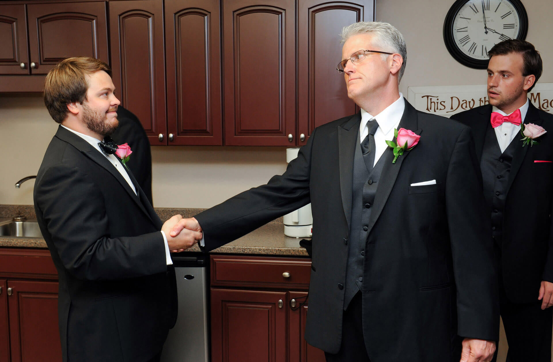 Th father of the bride clutches the groom's hand with a menacing look before the groom's Macomb County, Michigan wedding.