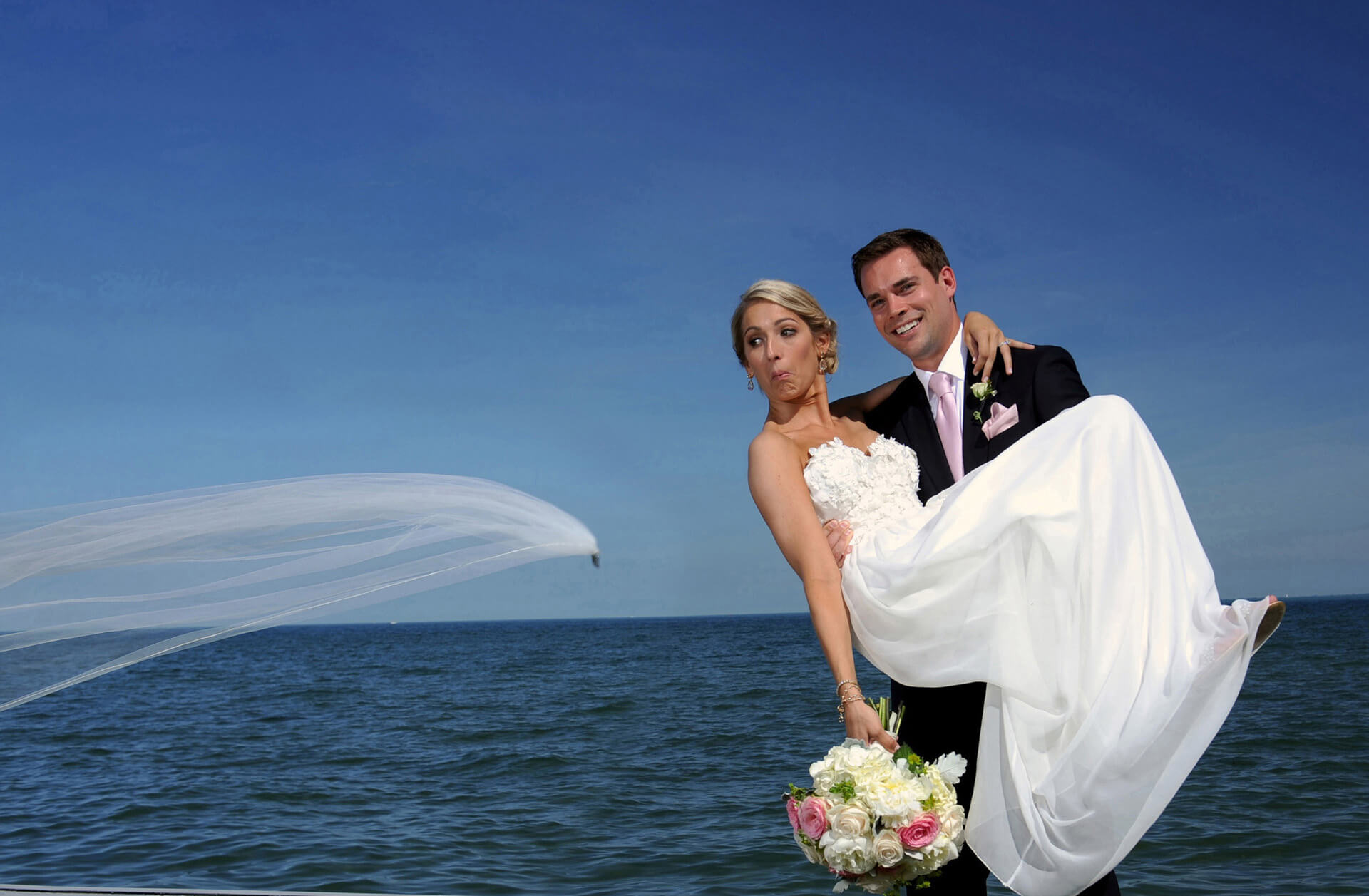 A beautiful Grosse Pointe Michigan wedding couple react as the bride's veil pulls away from her and heads to the water in Grosse Pointe Michigan after their wedding.