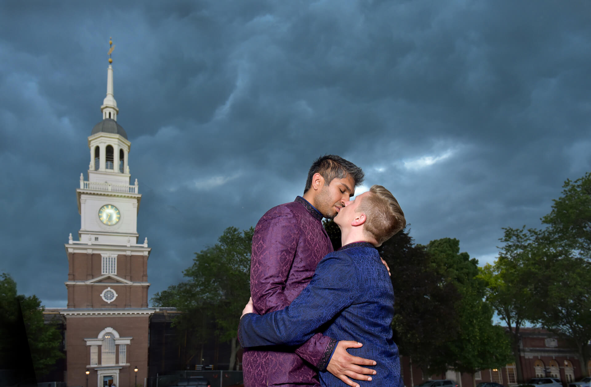 Wedding photojournalist Marci Curtis captures moments during her wedding photography like this same sex couple sneaking a quick kiss in before the storm hits their Henry Ford Museum wedding in Dearborn, Michigan.