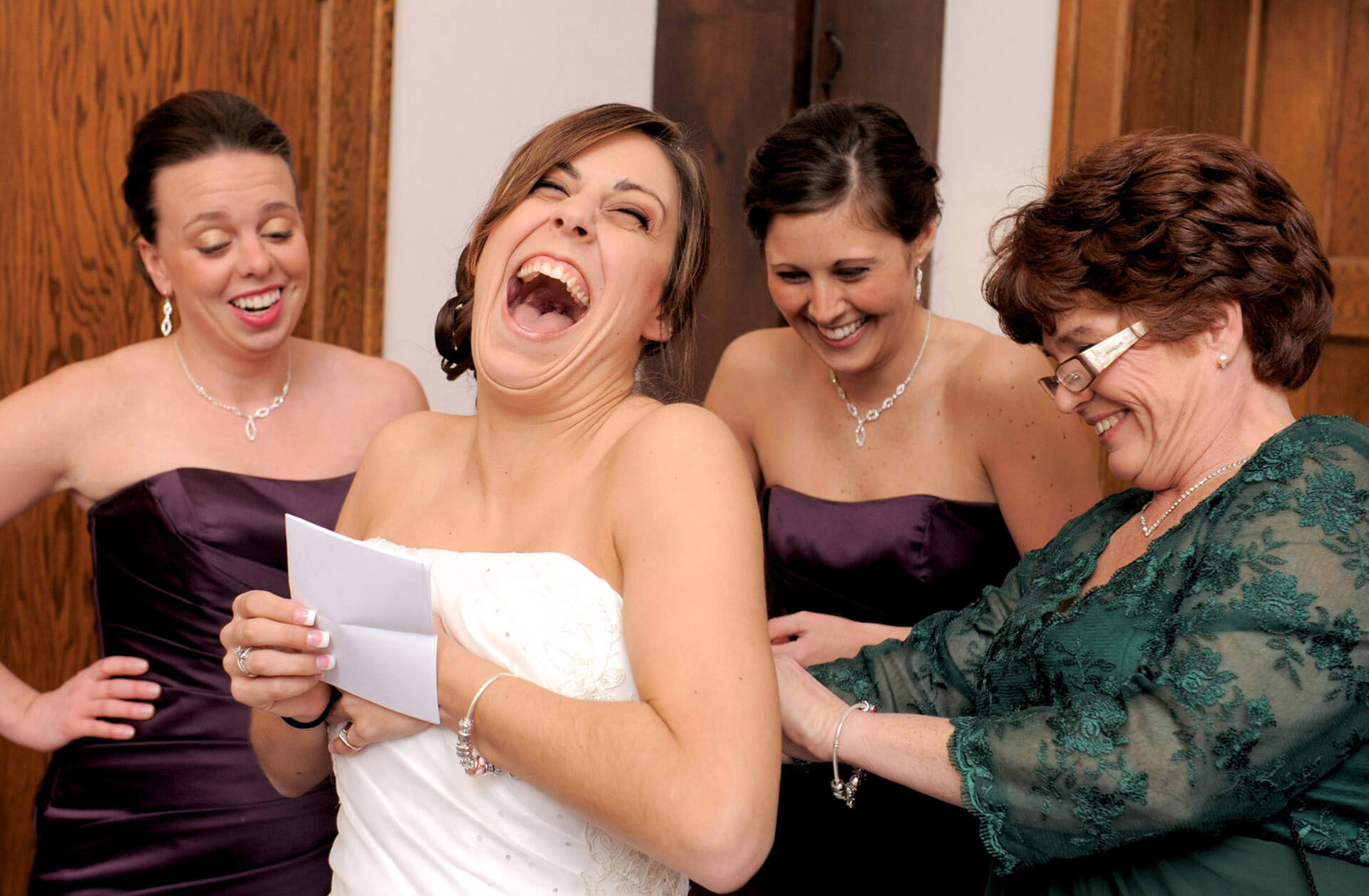 An Ypsilanti, Michigan bride laughs as she tries to read her romantic letter from her husband while being zipped into her dress on her wedding day.