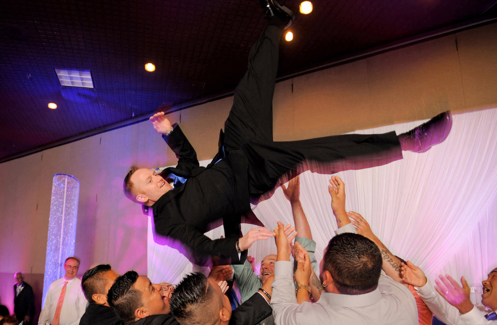 A Sterling Heights, Michigan groom goes flying during the wedding reception during this candid wedding photography moment in the metro Detroit area of Michigan.