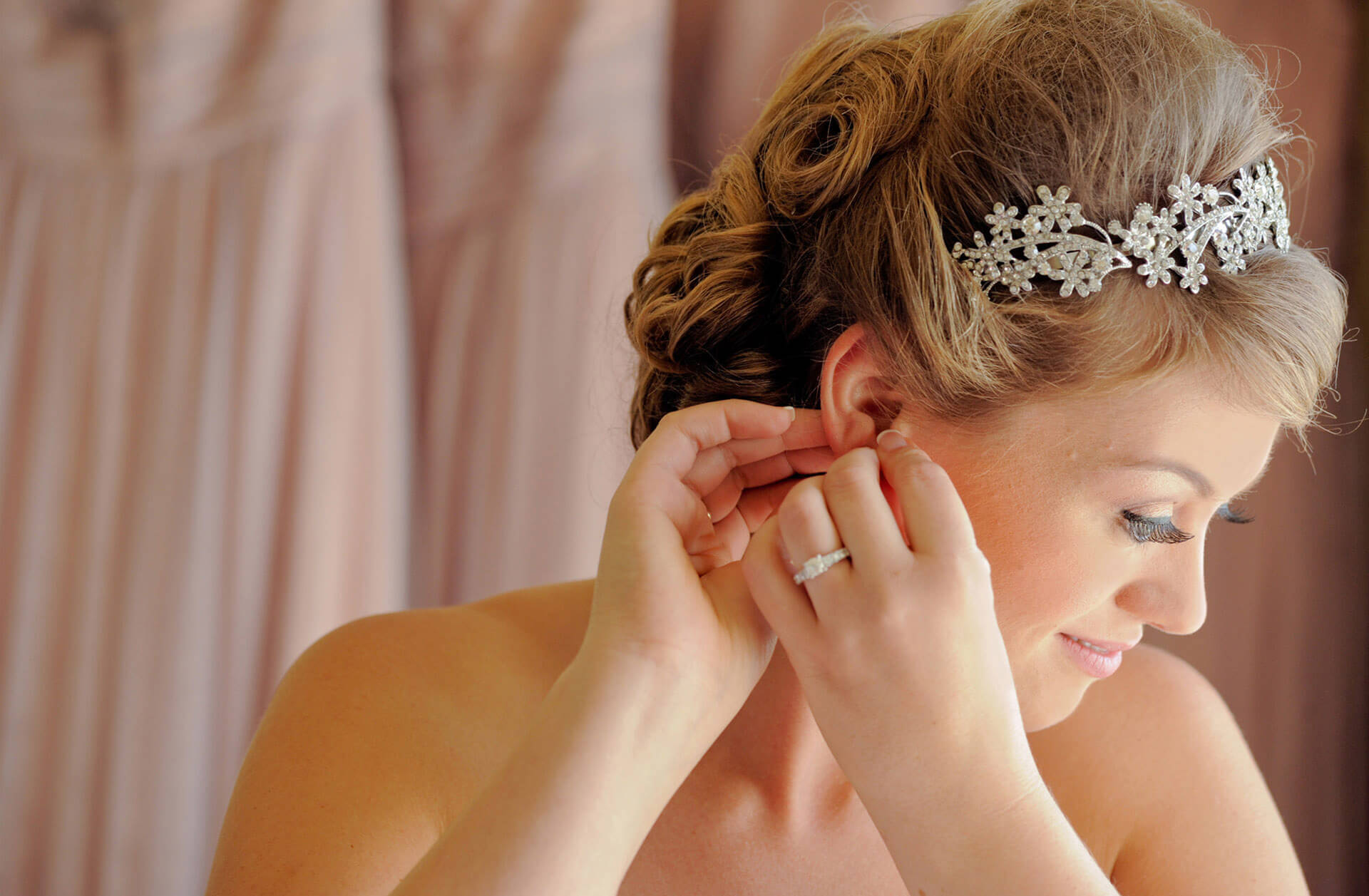 A bride fiddles with her earring as she gets ready at a hotel before her wedding in the Metro Detroit area.