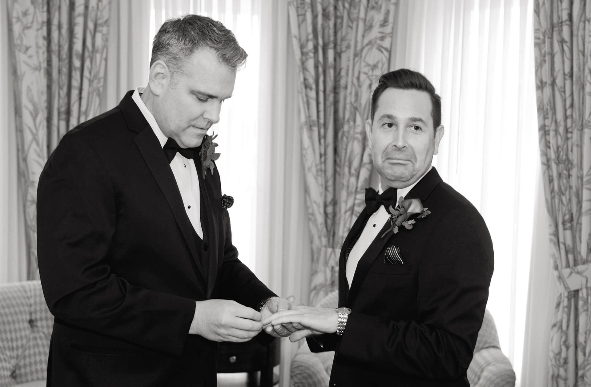 Wedding photojournalist Marci Curtis captures moments during her wedding photography like this groom's reaction as his husband practices placing the ring on his finger in Rochester, Michigan.