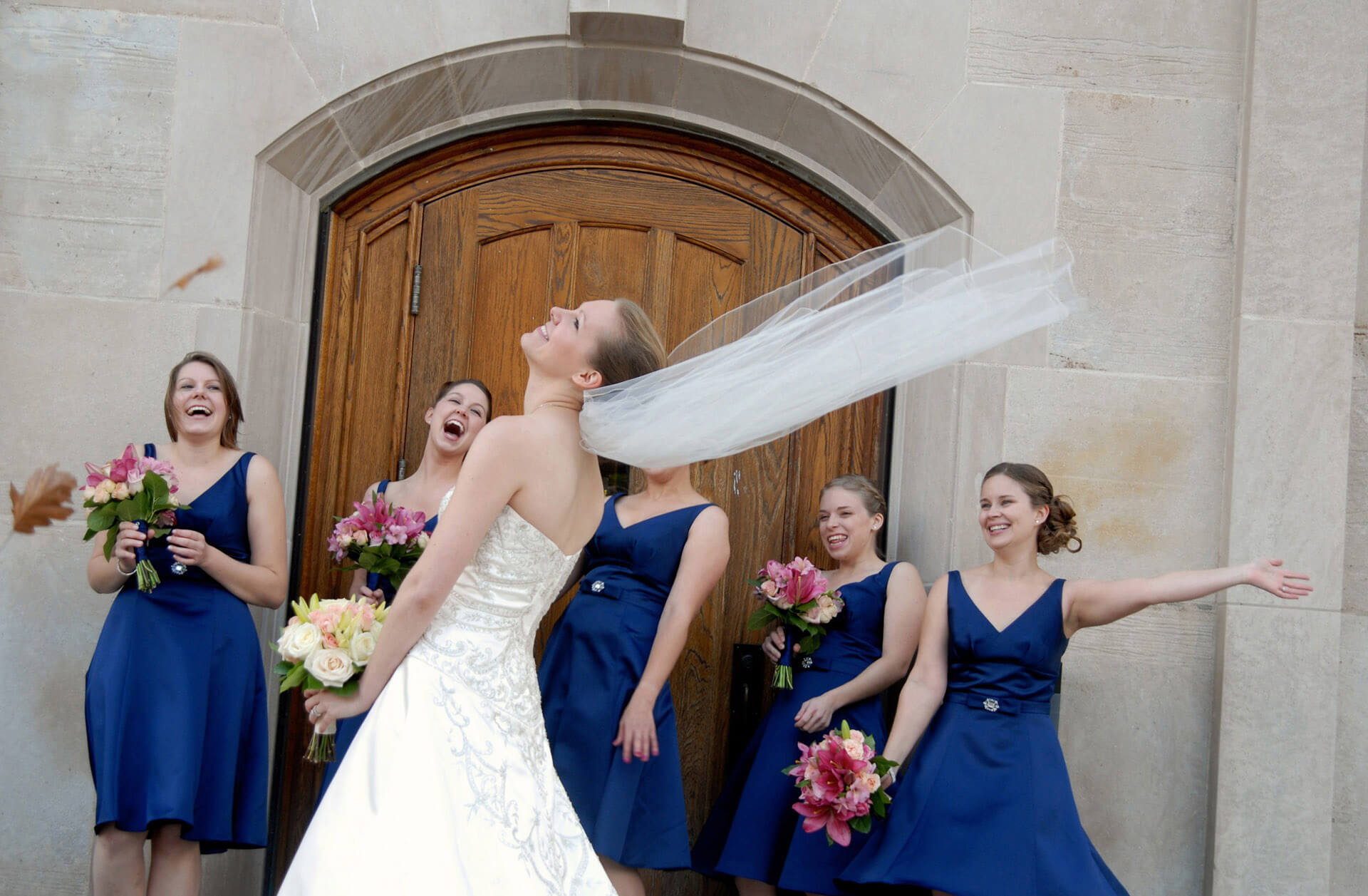 A Michigan bride laughs as the wind takes her veil in the wind during a fall wedding in Ann Arbor, Michigan.